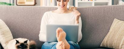 Junge Frau beim Onlineshoppen am Laptop mit Katze auf dem Sofa