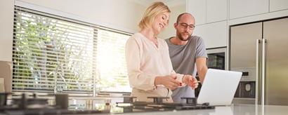 Glückliches Paar am Laptop in der Küche