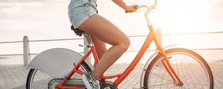 Junge Frau auf einem orangen Fahrrad im Close-up