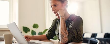 Junge Frau vor Laptop an ihrem Schreibtisch
