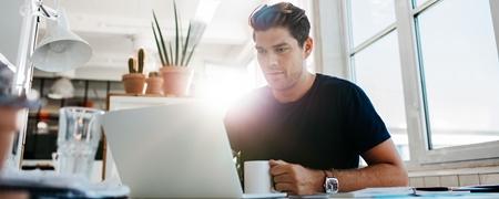 Junger Geschäftsmann arbeitet am Laptop