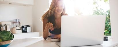 Junge Frau in ihrer Küche vor dem Laptop