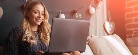 Lächelnde junge blonde Frau sitzt mit Laptop auf den Knien im Bett