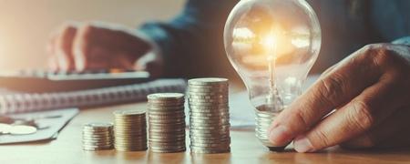 Mann an Schreibtisch mit Taschenrechner, gestapelten Münzen und Glühbirne
