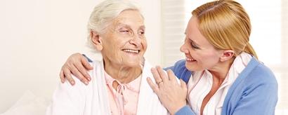 Lachende Seniorin auf Bett sitzend schaut ihre Tochter an