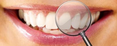 Lächelnder weiblicher Mund in Nahaufnahme mit Lupe