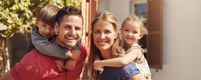 Lächelnde Eltern tragen ihre Kinder im Huckepack