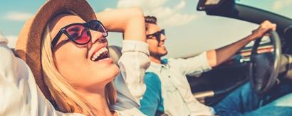 Junges lachendes Paar in Cabrio unterwegs im Sonnenschein