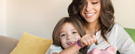 Mutter und Tochter sitzen auf dem Sofa und füttern ein Sparschwein lächelnd mit Münzen