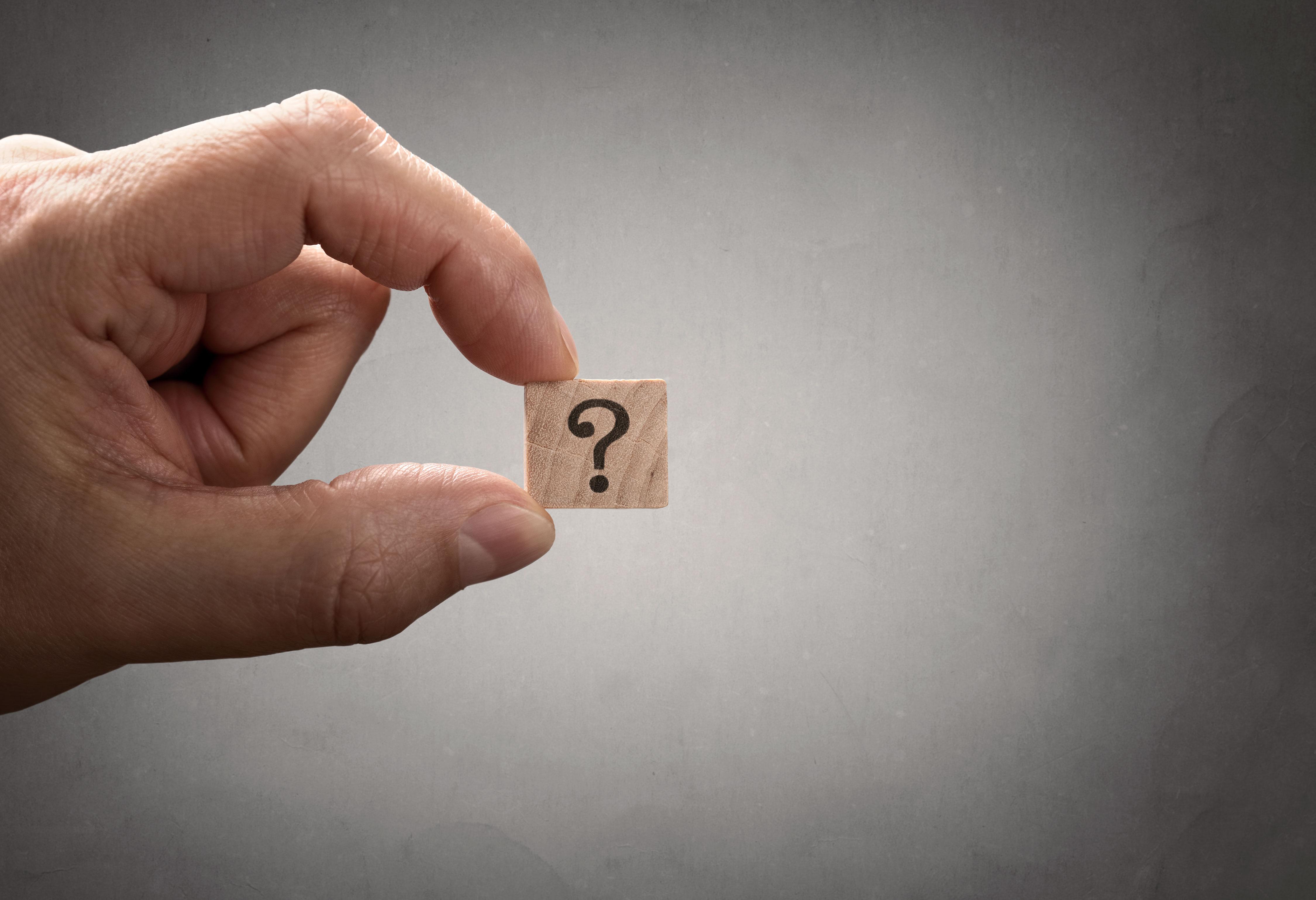 Block mit Fragezeichen zwischen Fingern vor grauem Hintergrund