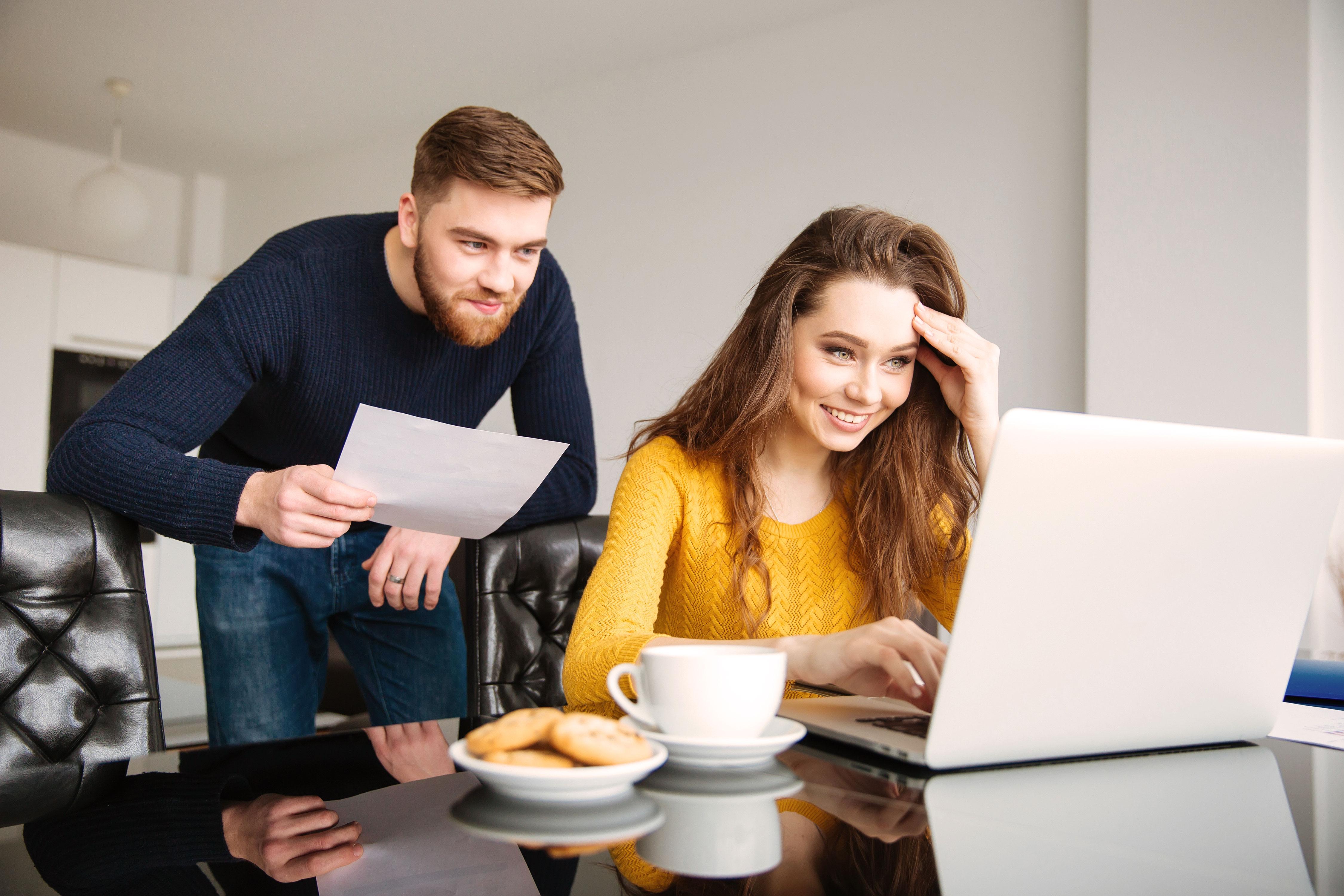 Junges Paar mit Rechnungen vor dem Laptop