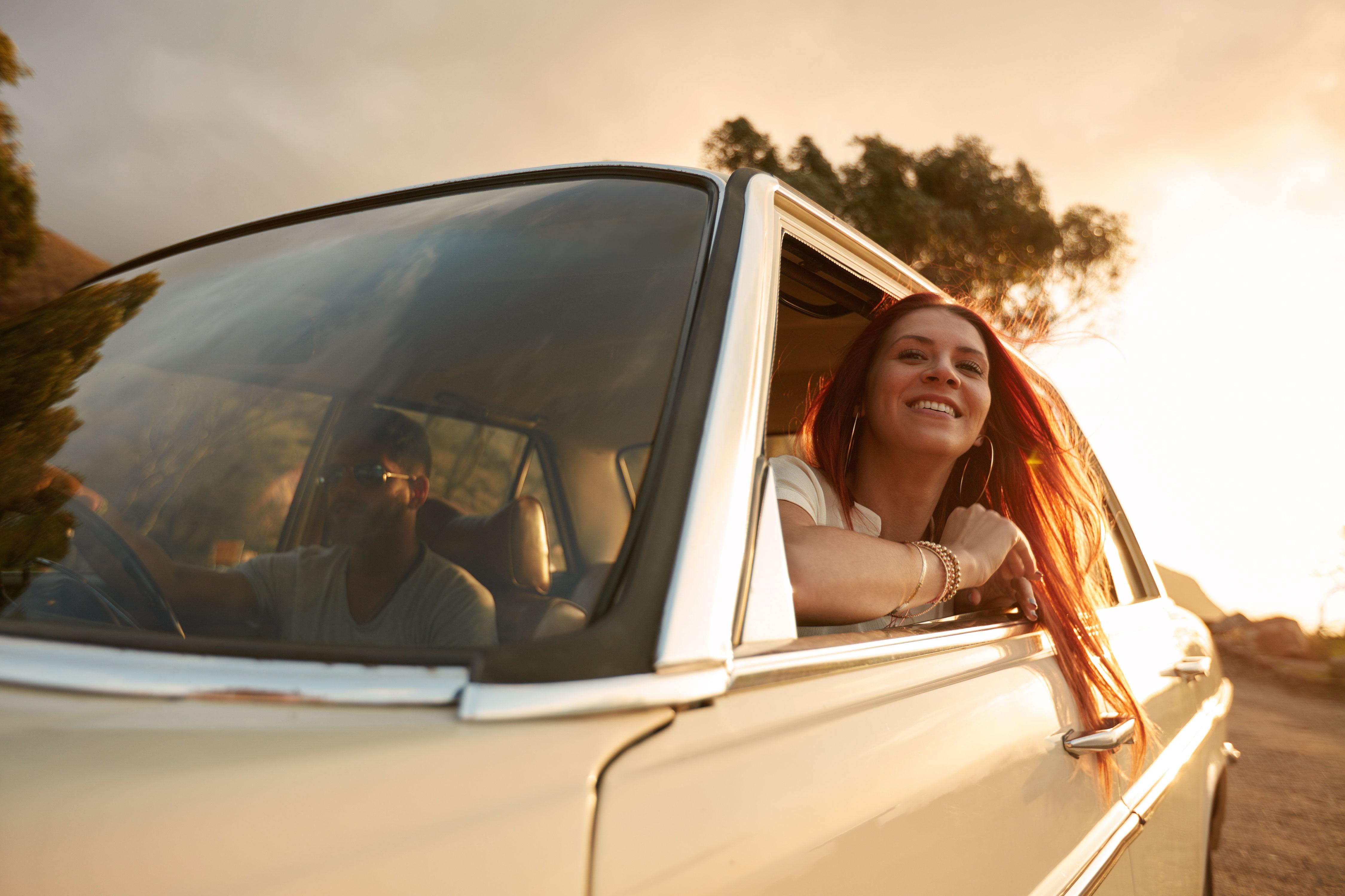 Junge Frau lehnt sich lächelnd aus Beifahrerfenster