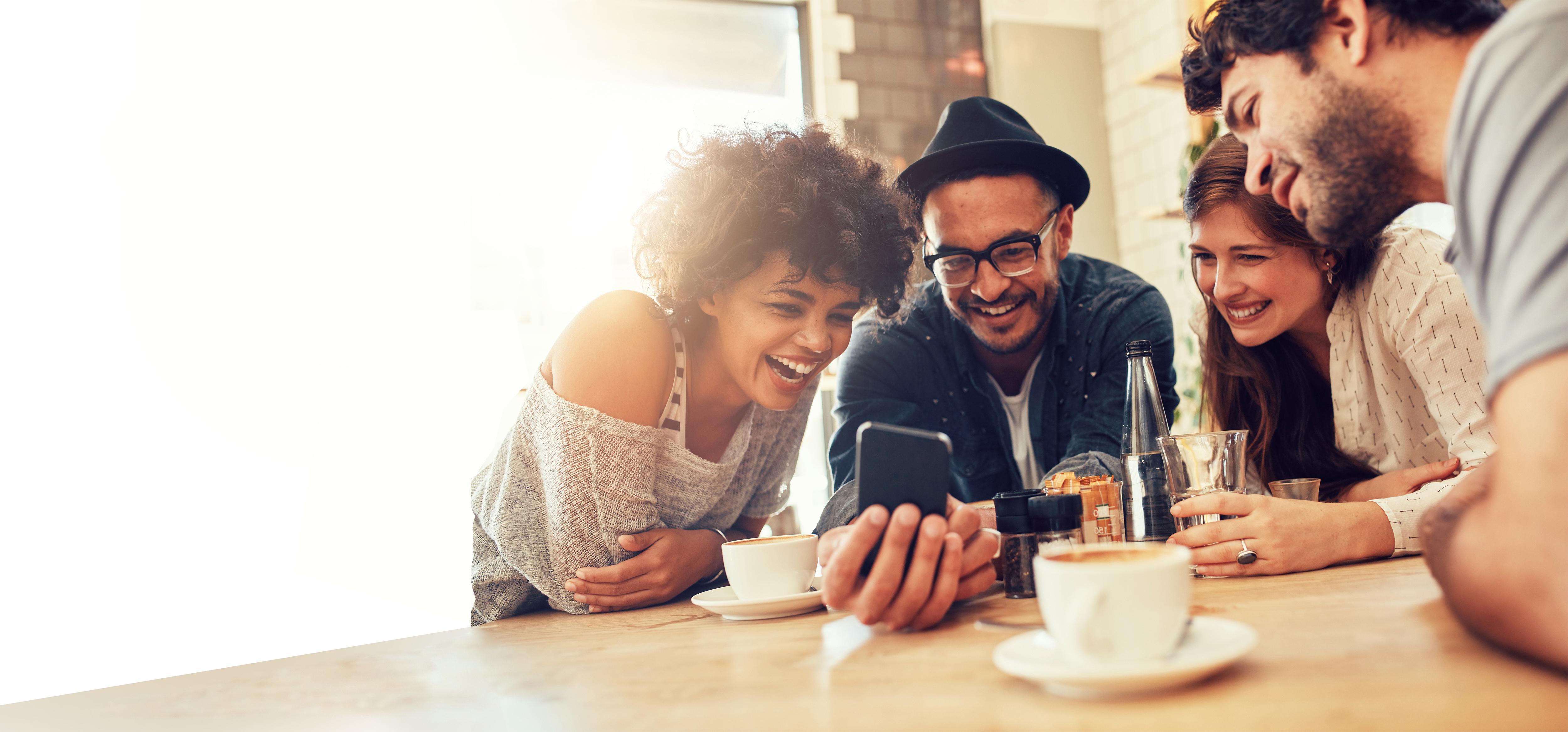 Gruppe junger Menschen am Tisch mit Handy