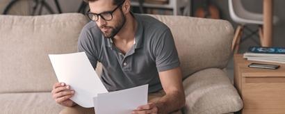 Junger Mann auf Sofa mit Dokumenten in den Händen
