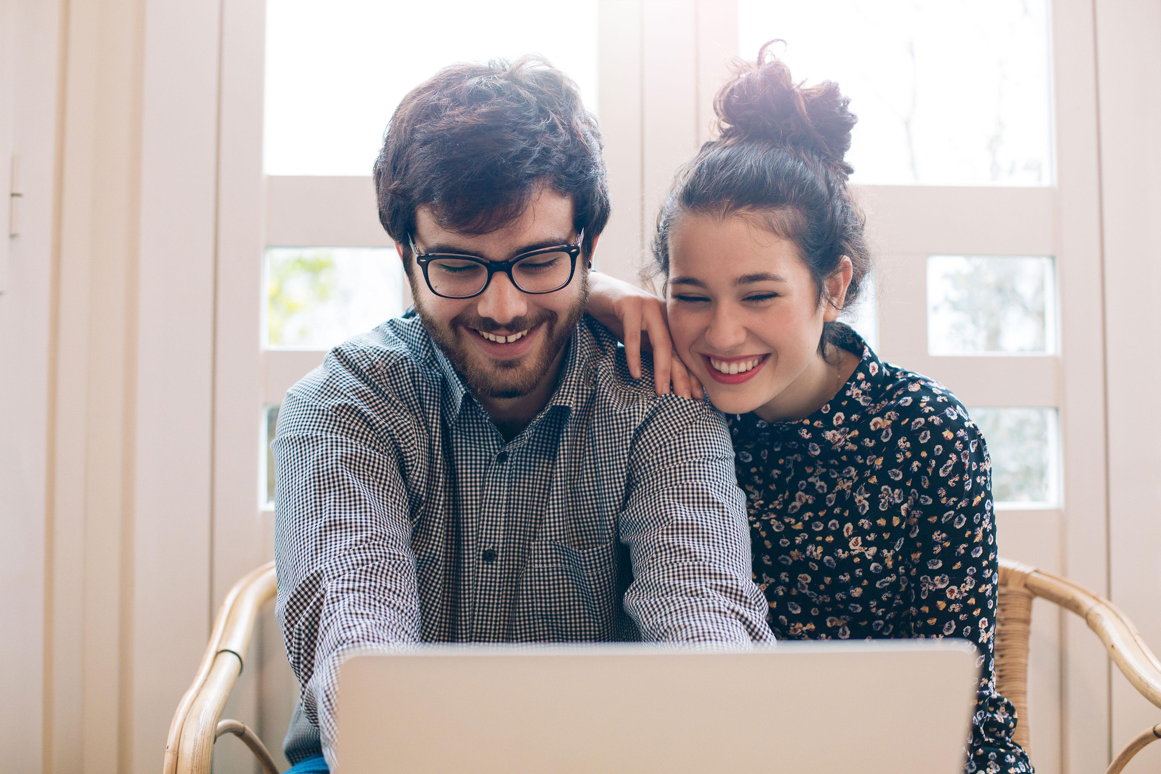 Junges lächelndes Paar am Laptop vor dem Fenster