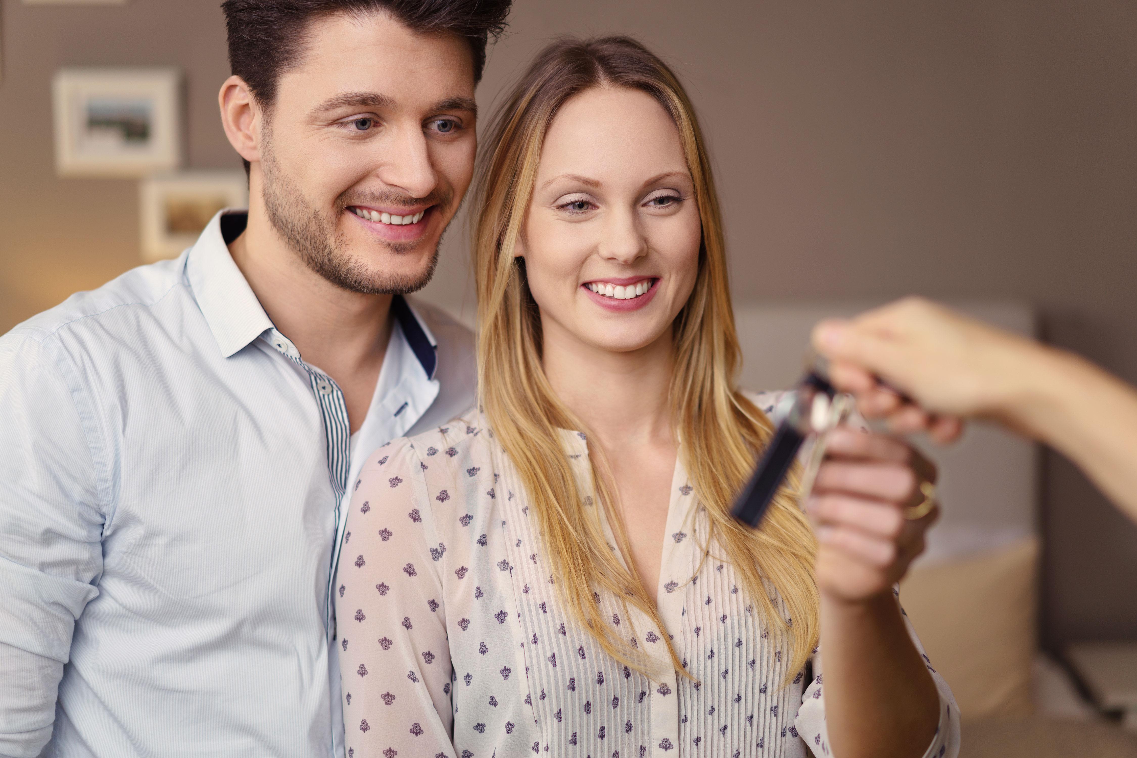 Junges glückliches Paar erhält Schlüssel zur neuen Wohnung