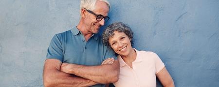 Älteres lächelndes Paar vor blauer Wand