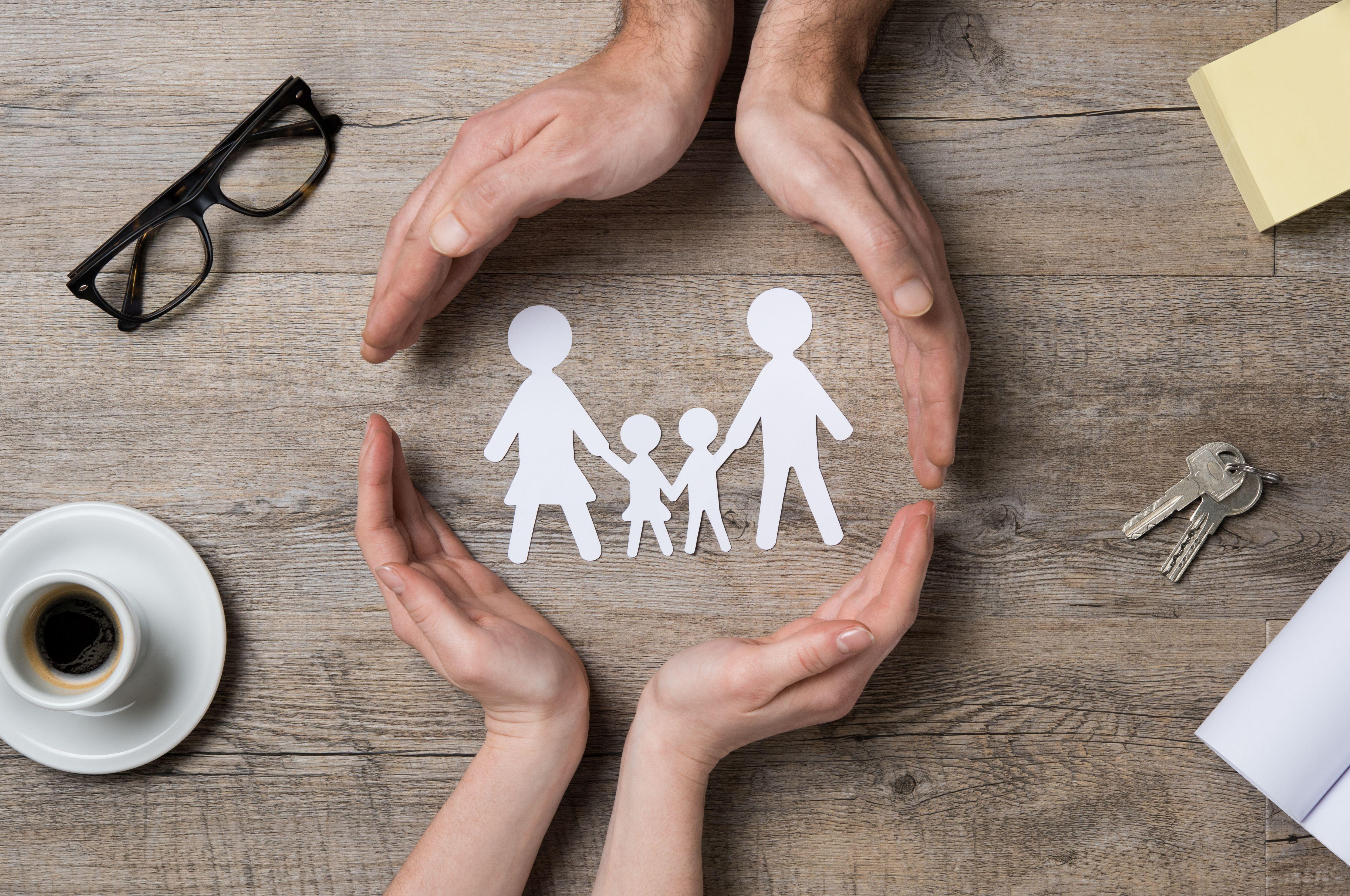 Papierfamilie umschlossen von Erwachsenen- und Kinderhänden