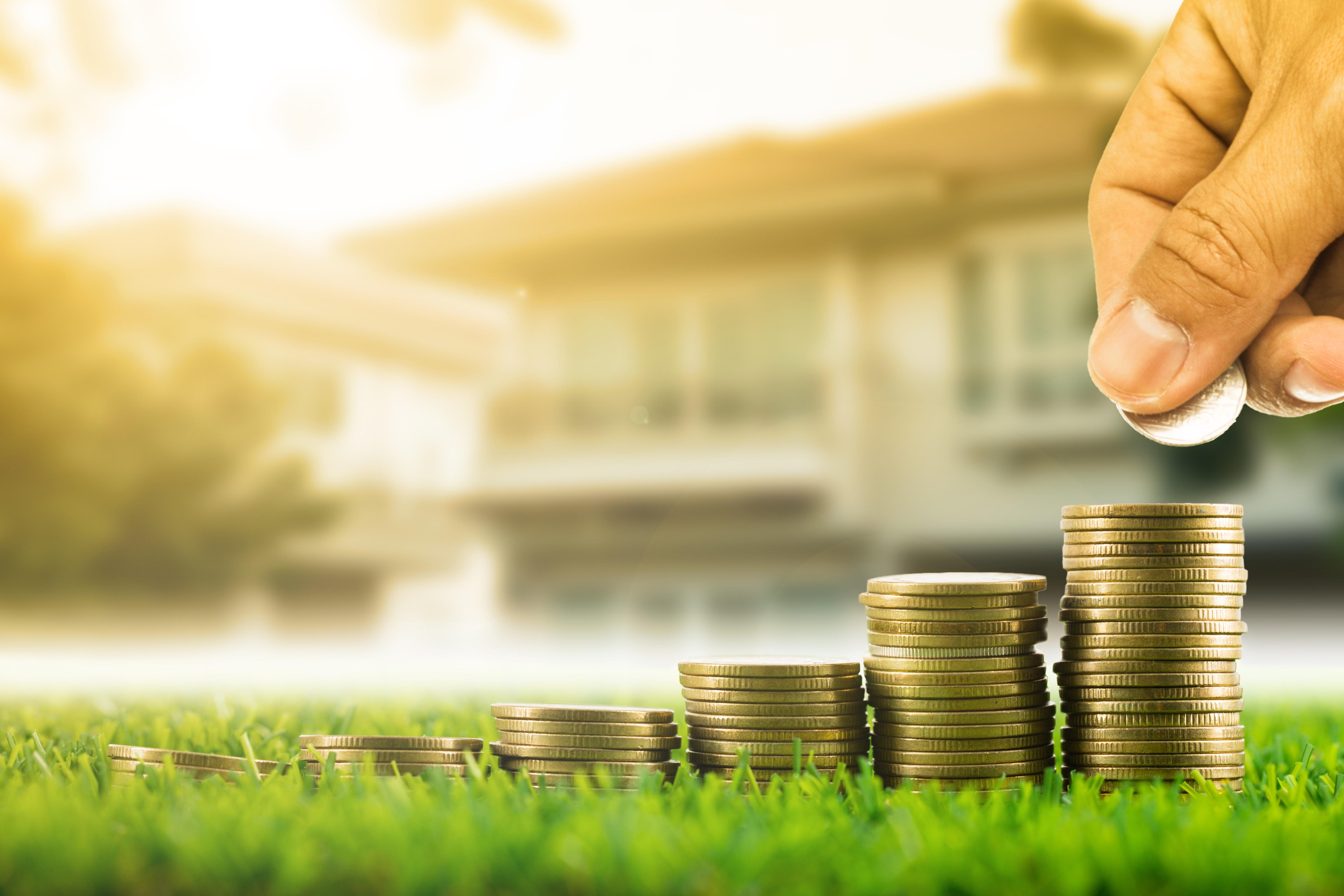 Hand stapelt Münzen vor Haus