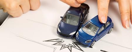 Mit Spielzeugautos simulierter Unfall auf gezeichneter Straße