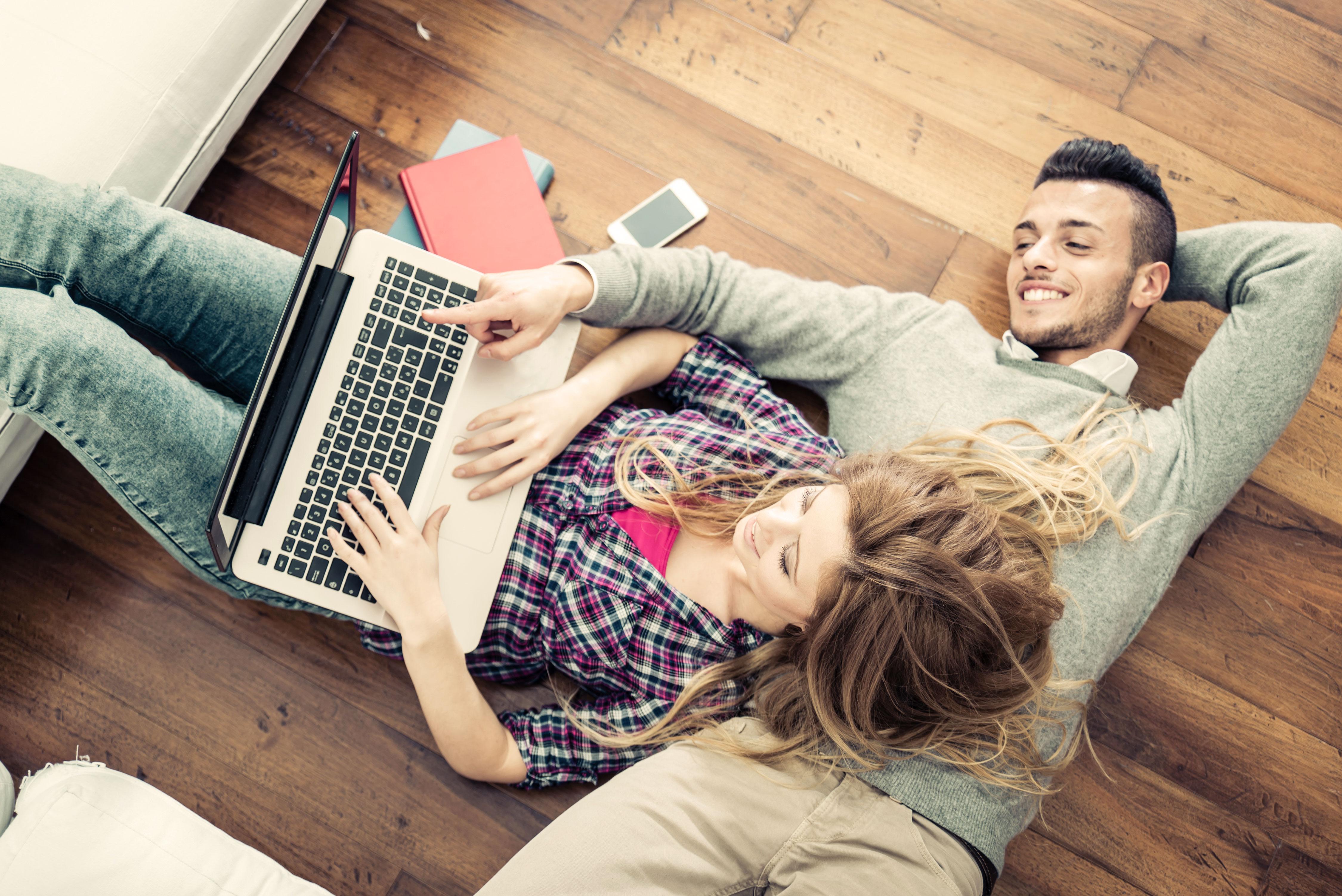 Lächelndes Paar auf Boden liegend am Laptop