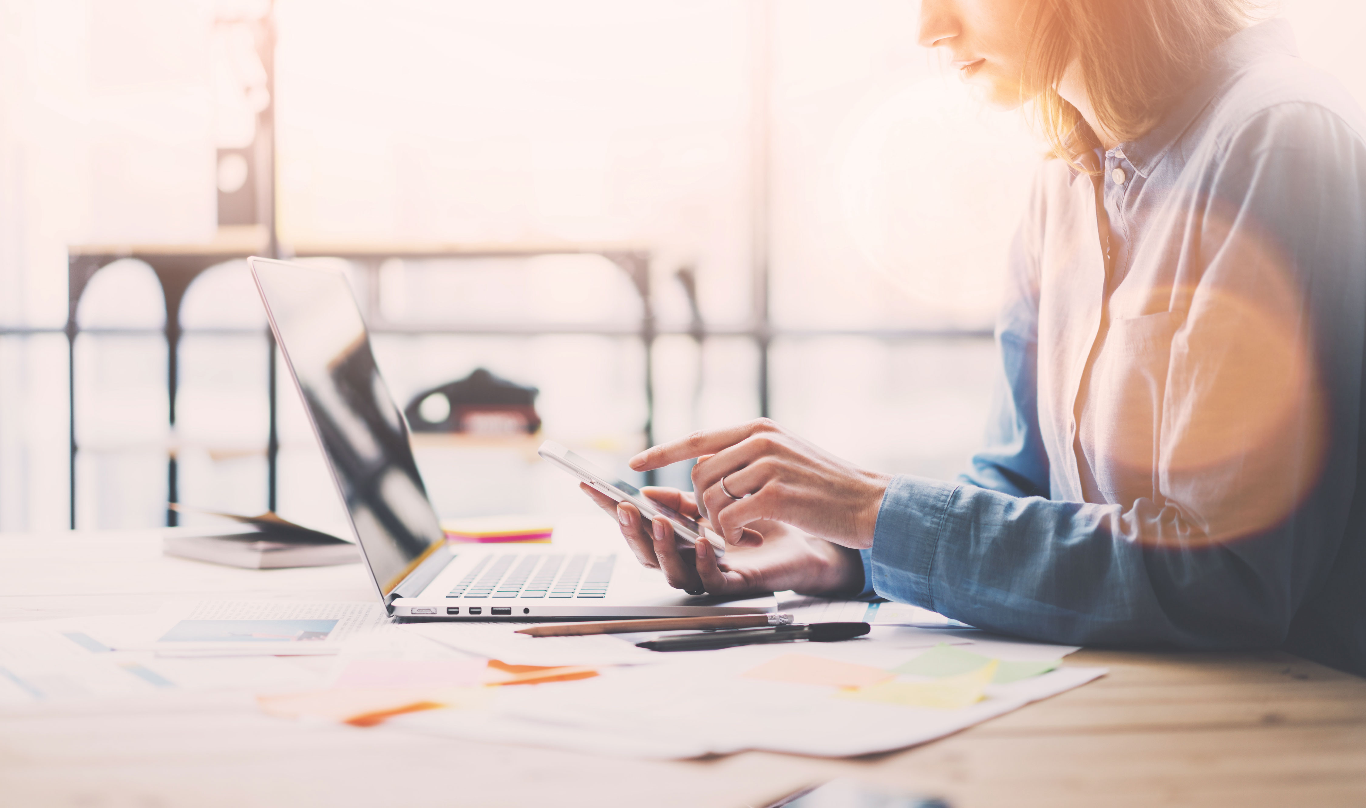 Businesswoman arbeitet an Projekt vor Smartphone und Laptop an Holztisch