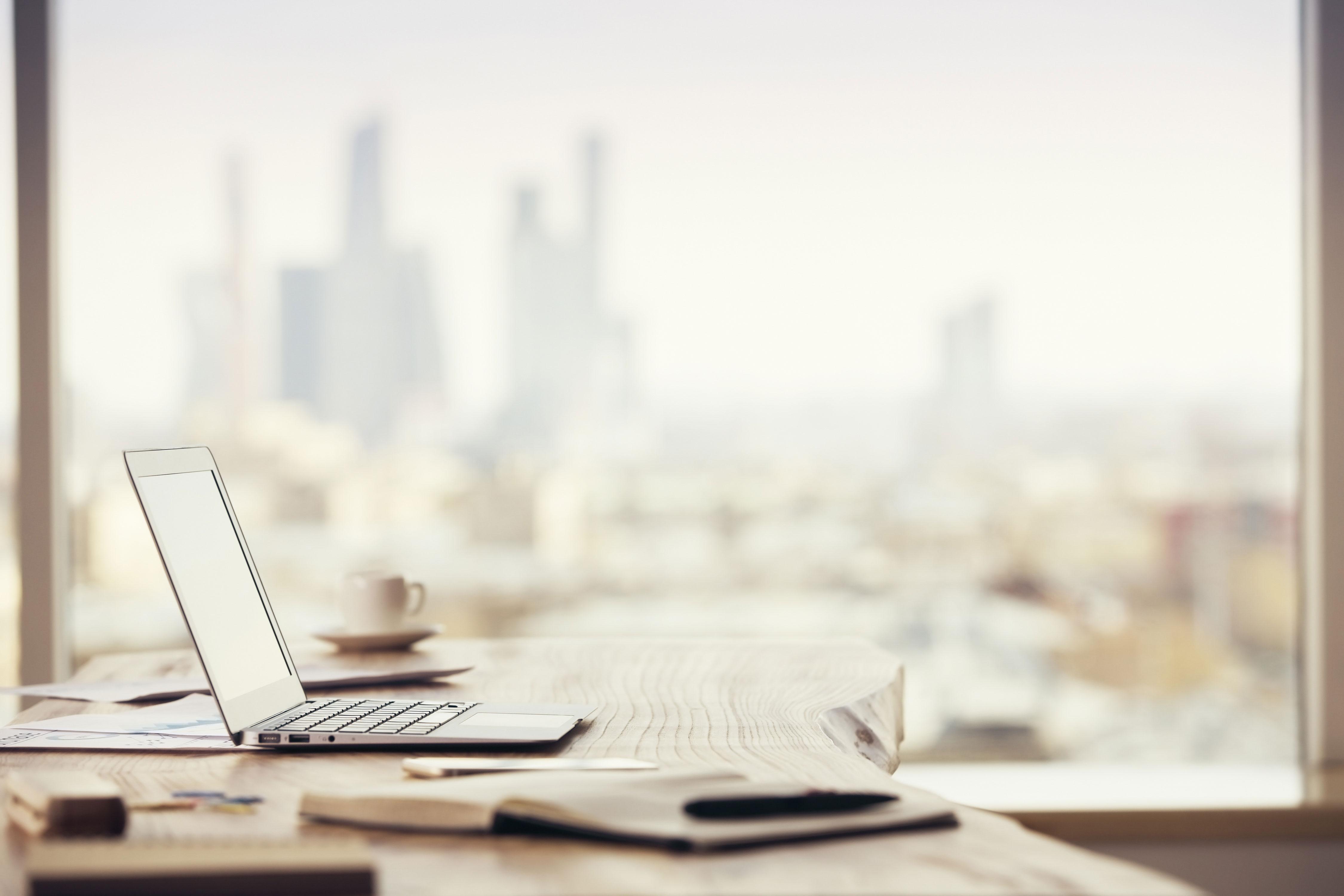 Schreibtisch mit Laptop vor Fenster
