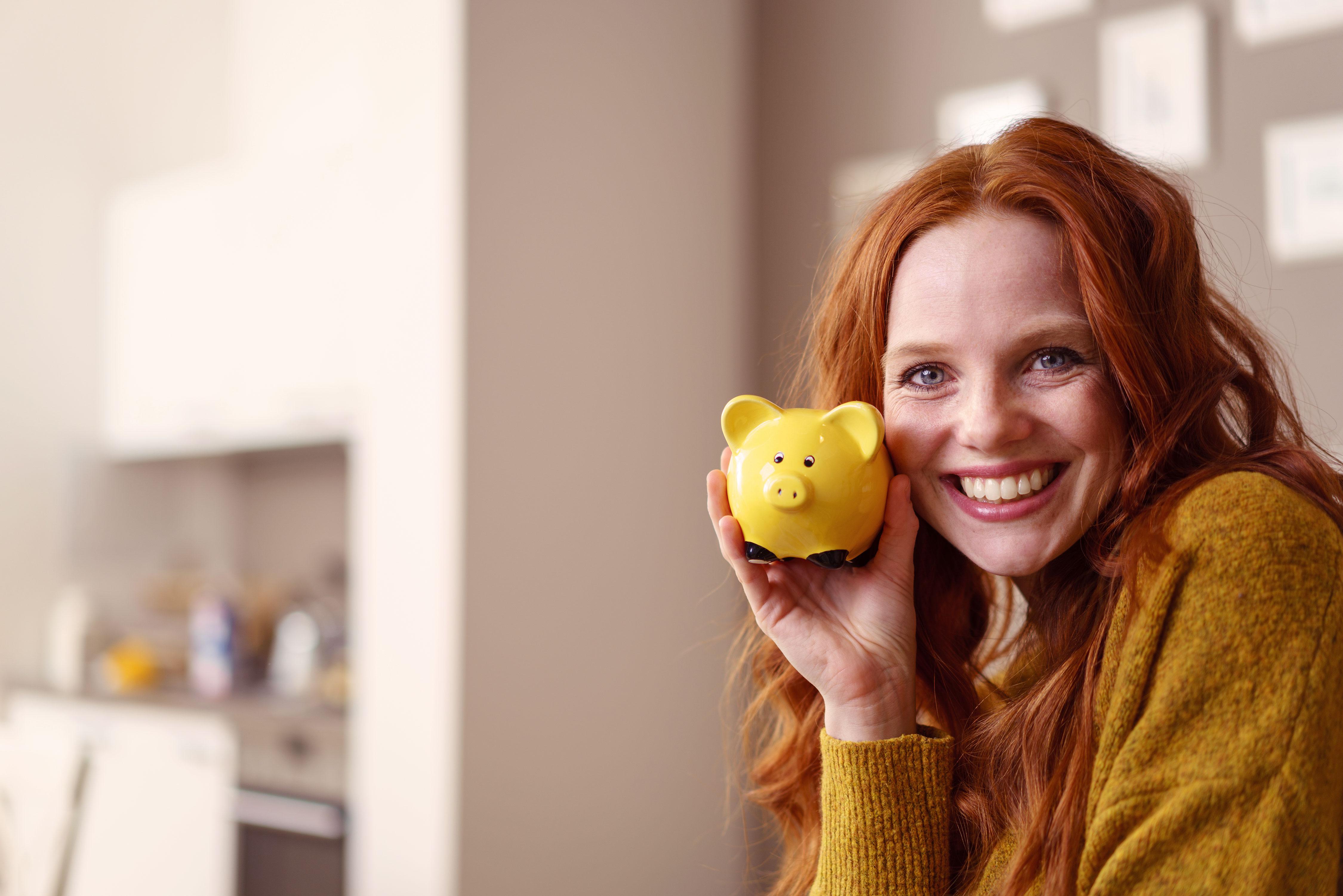 Lächelnde junge Frau hält Sparschwein in der Hand