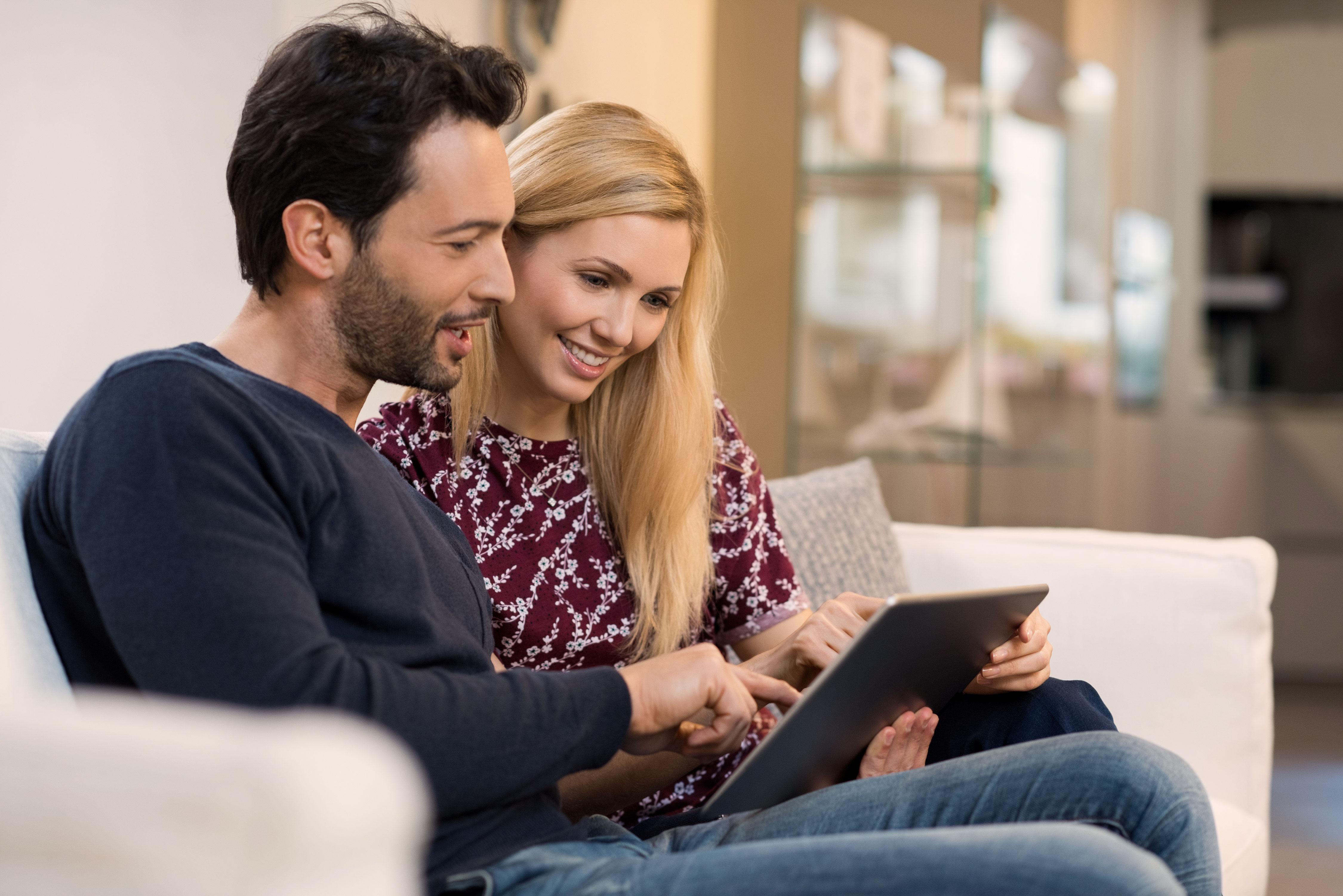 Junges Paar sitzt auf dem Sofa und surft auf dem Tablet
