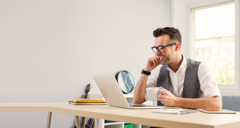 Lächelnder Mann vor Laptop an seinem Schreibtisch