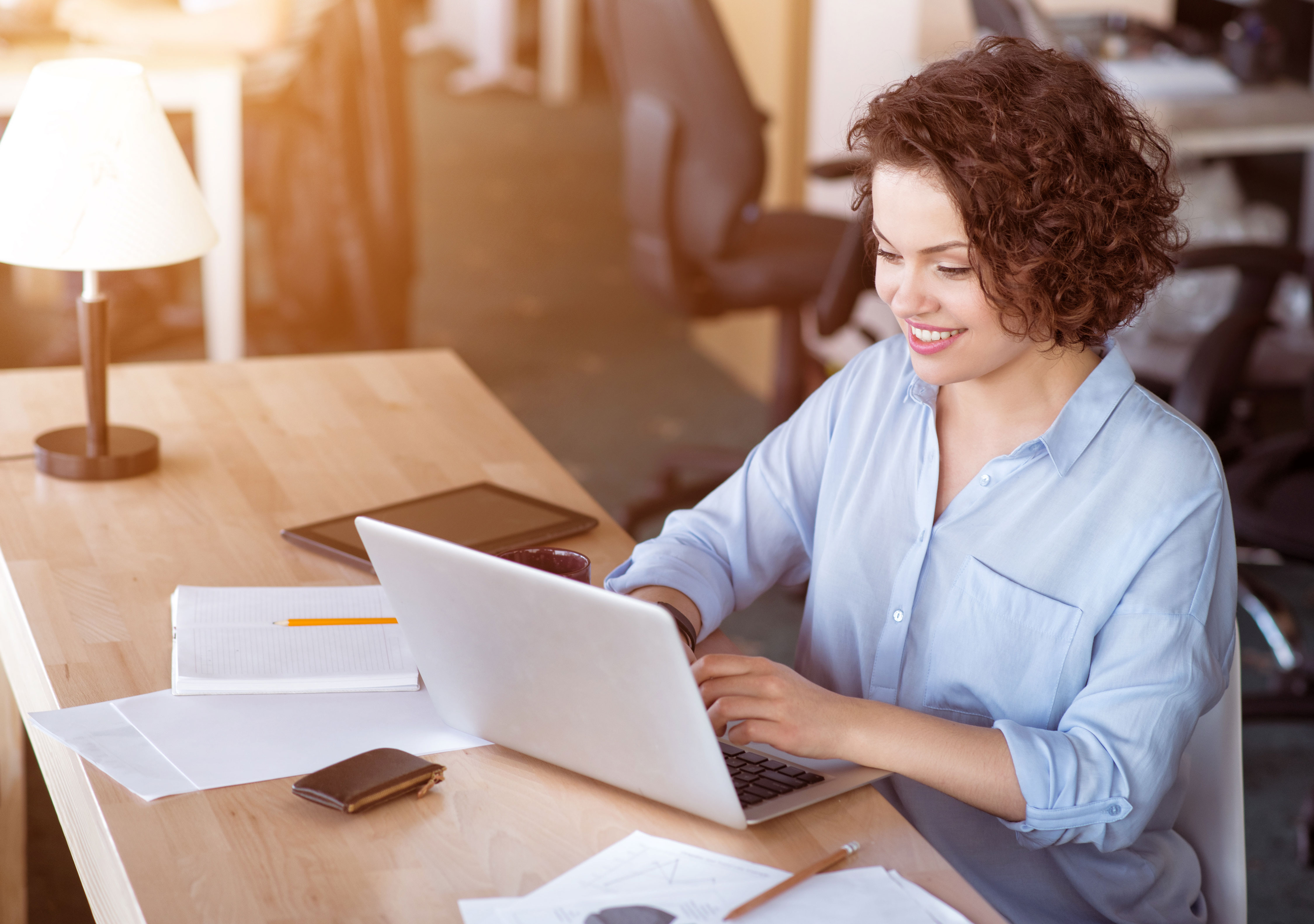 Businesswoman lächelnd vor Laptop an Schreibtisch