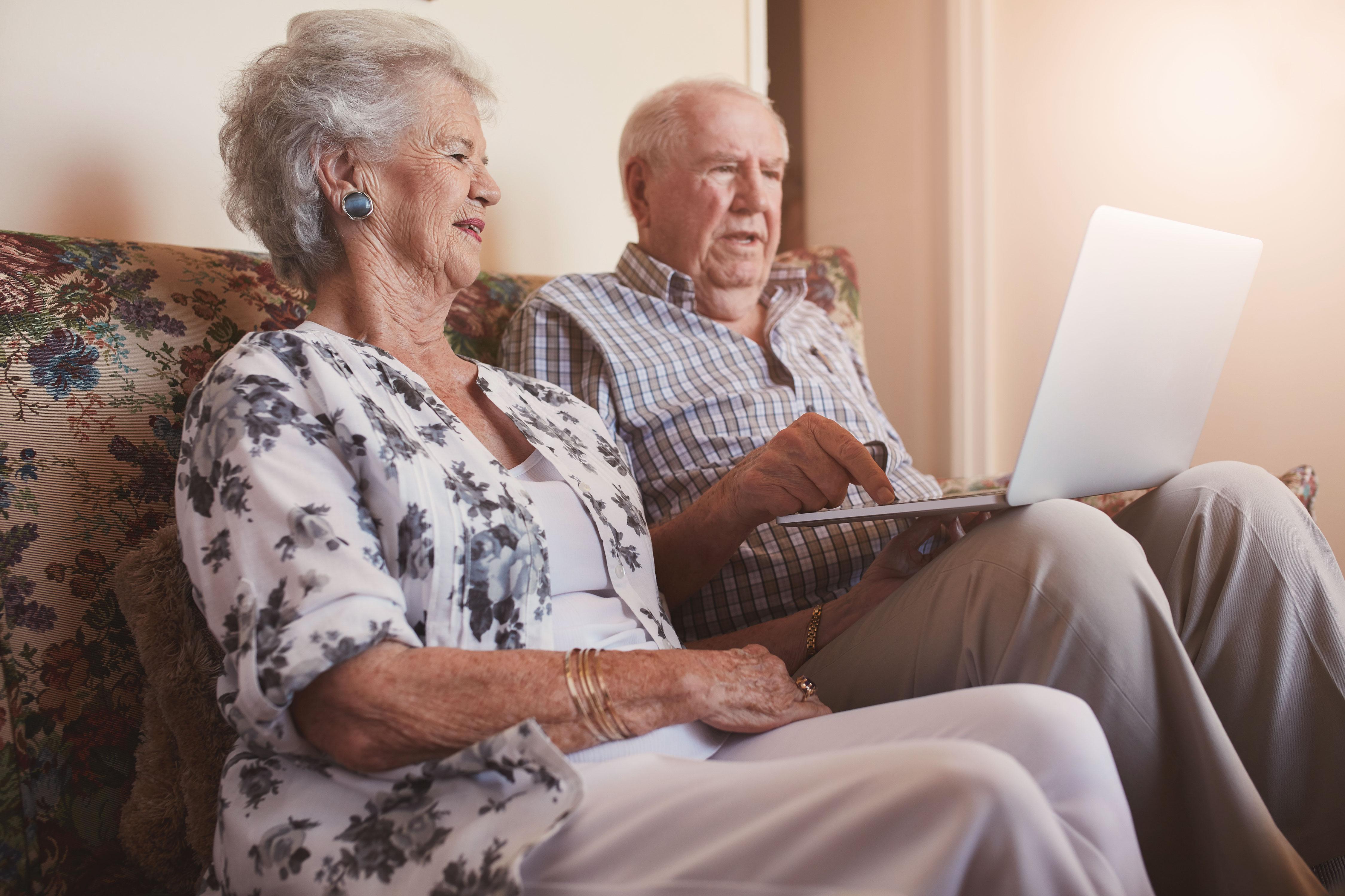 Älteres Paar sitzt auf dem Sofa mit dem Laptop