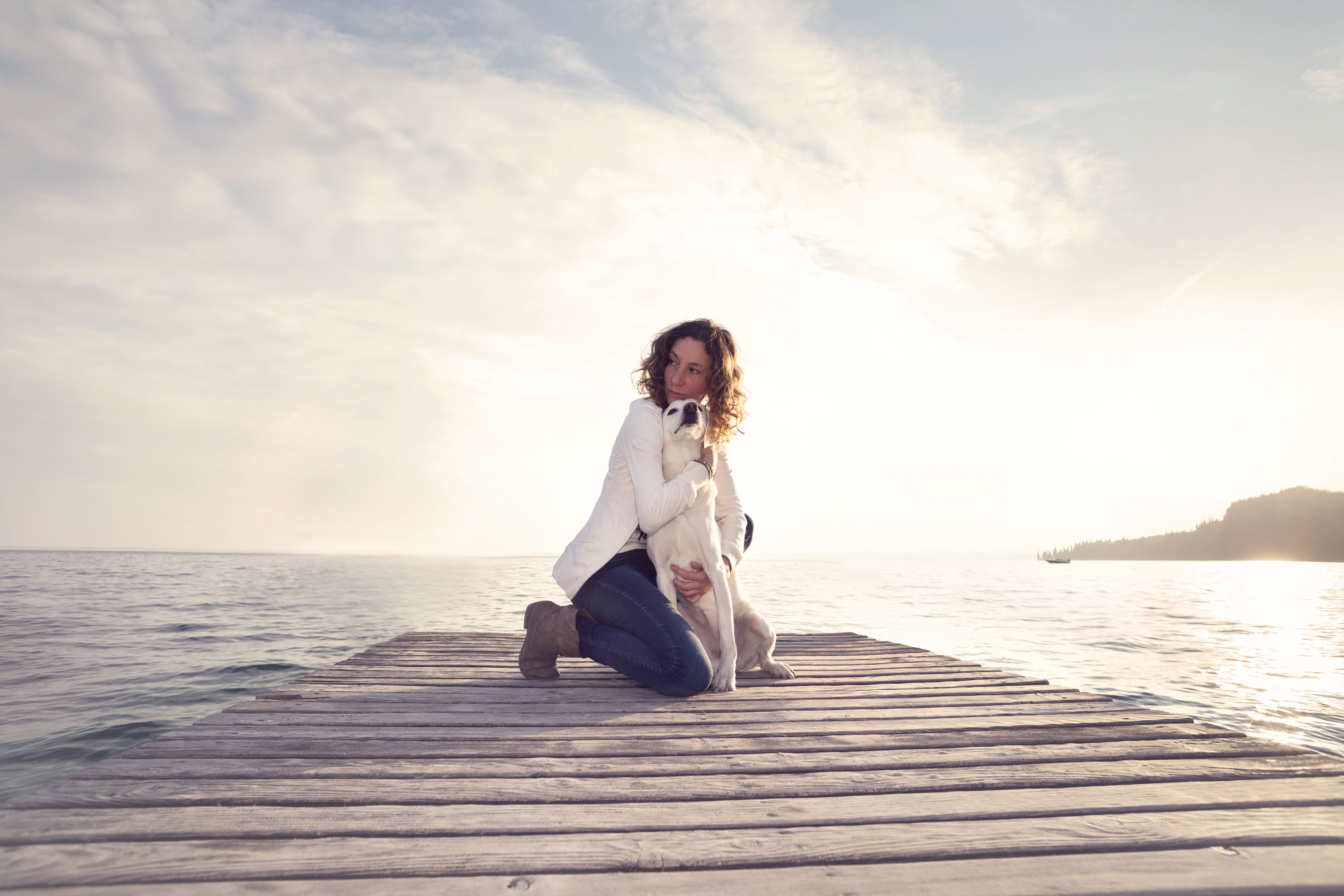 Frau umarmt Hund auf Steg zum Meer