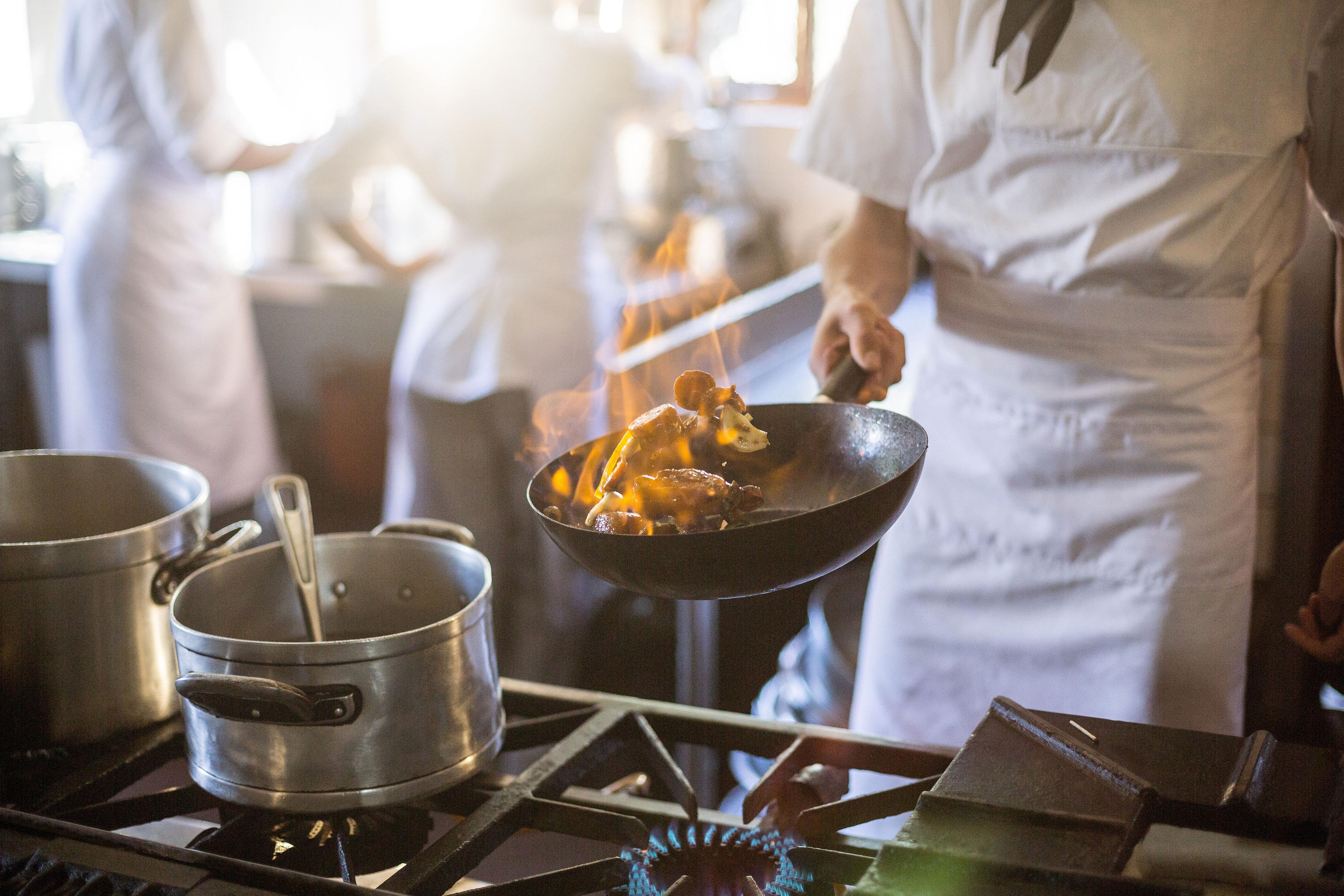 Koch vor Gasherd mit Pfanne beim Flambieren