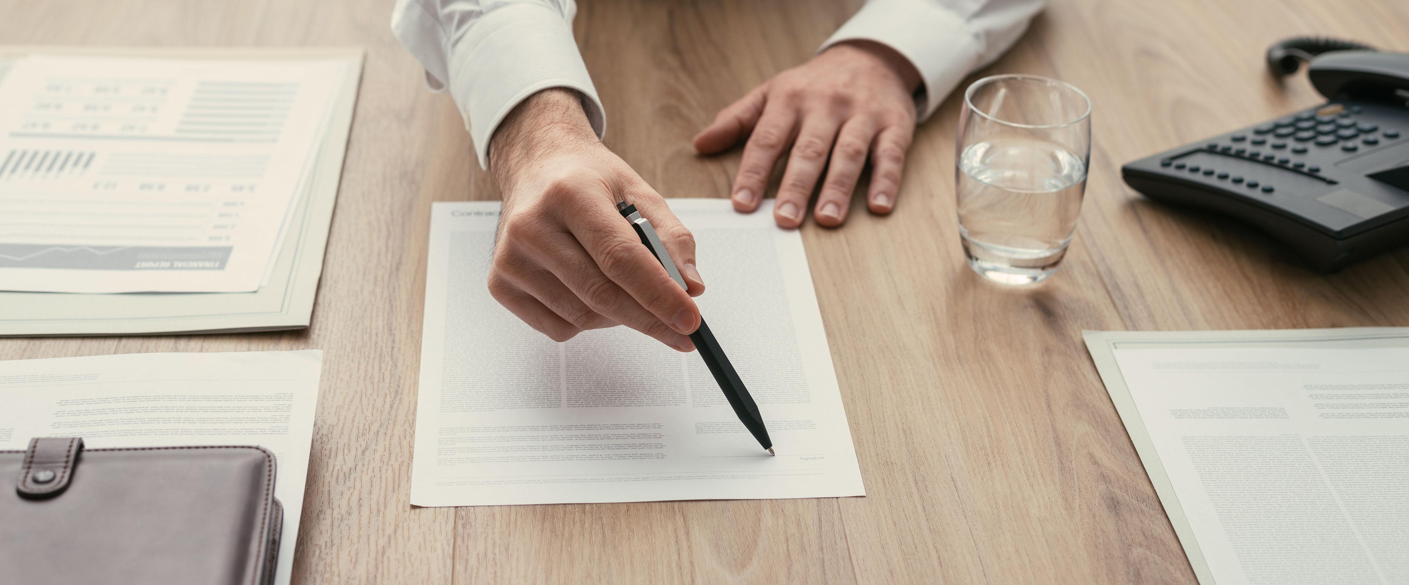 Hand mit Stift deutet auf Unterschriftenfeld in Dokument auf dem Schreibtisch