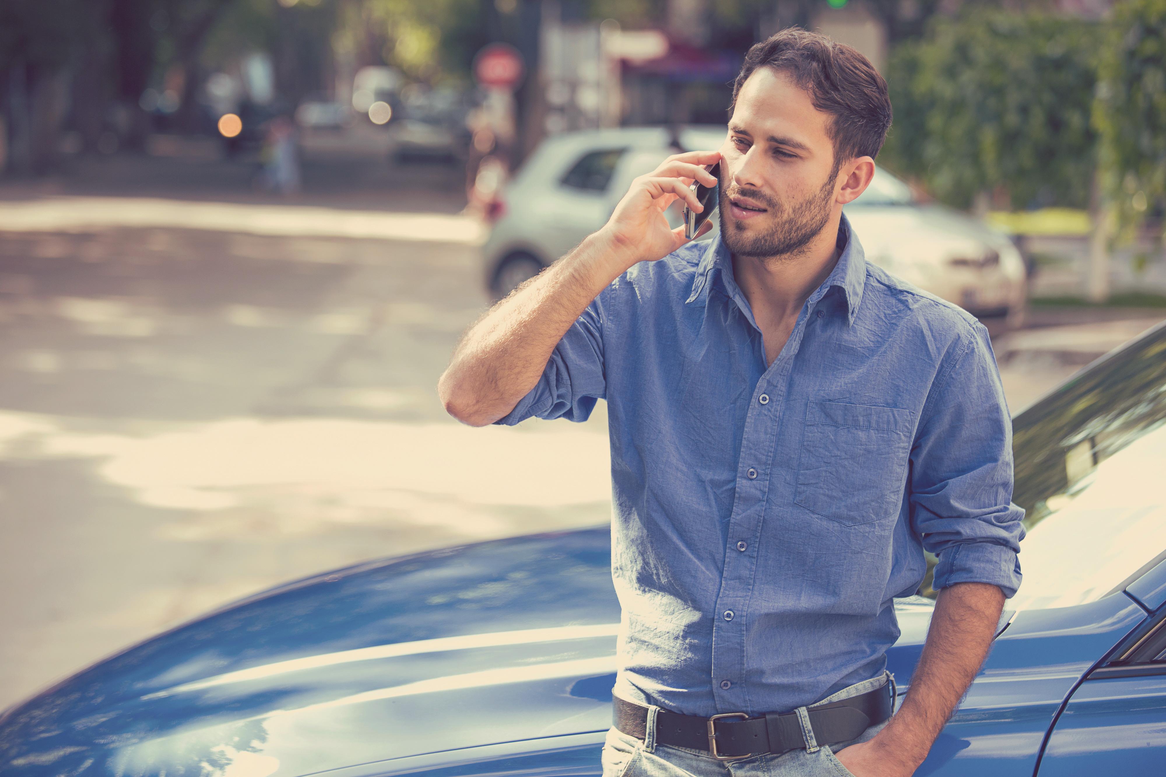 Junger Mann telefoniert mit seinem Handy an sein Auto gelehnt