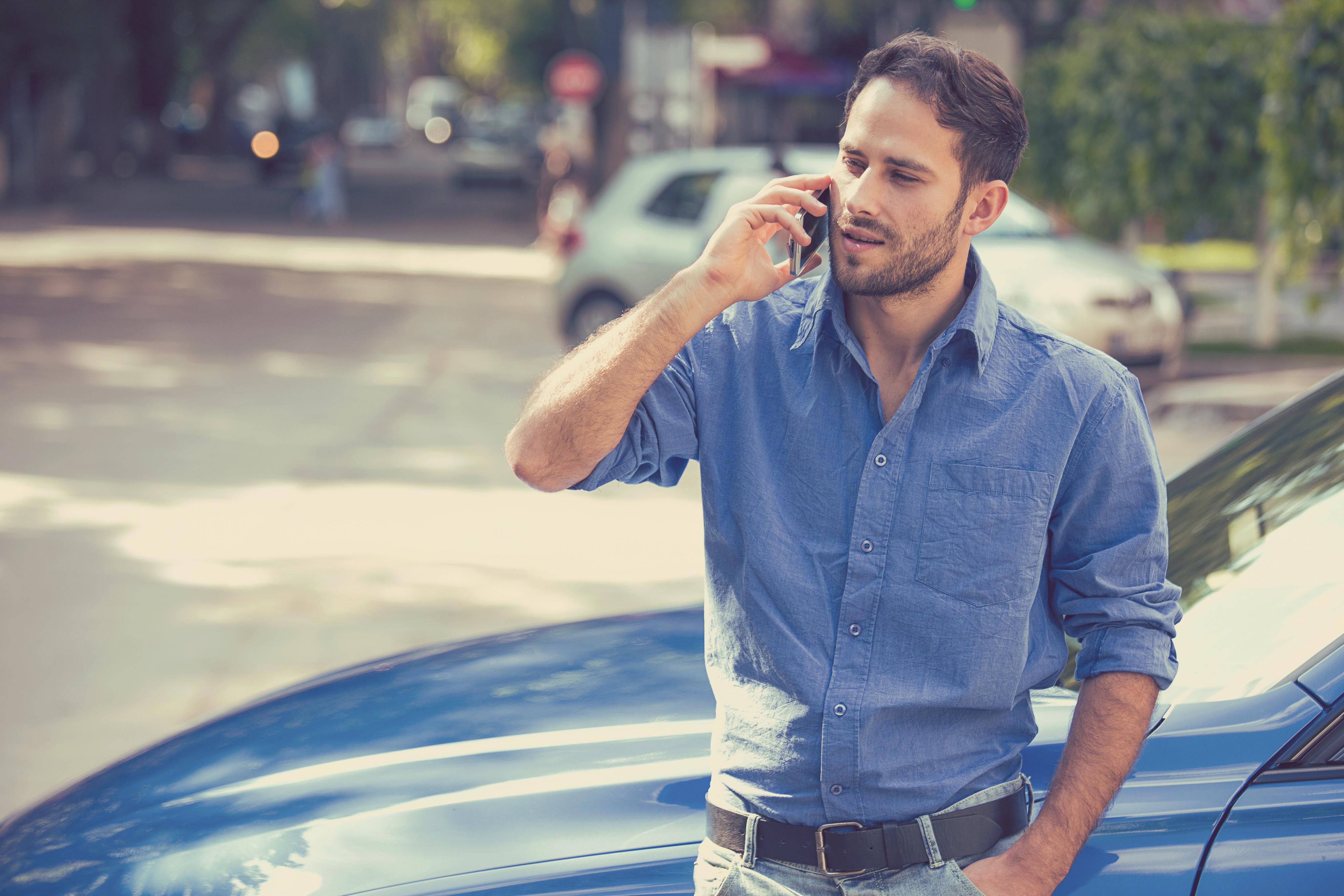Schadenservice, telefonierender Mann angelehnt an Auto