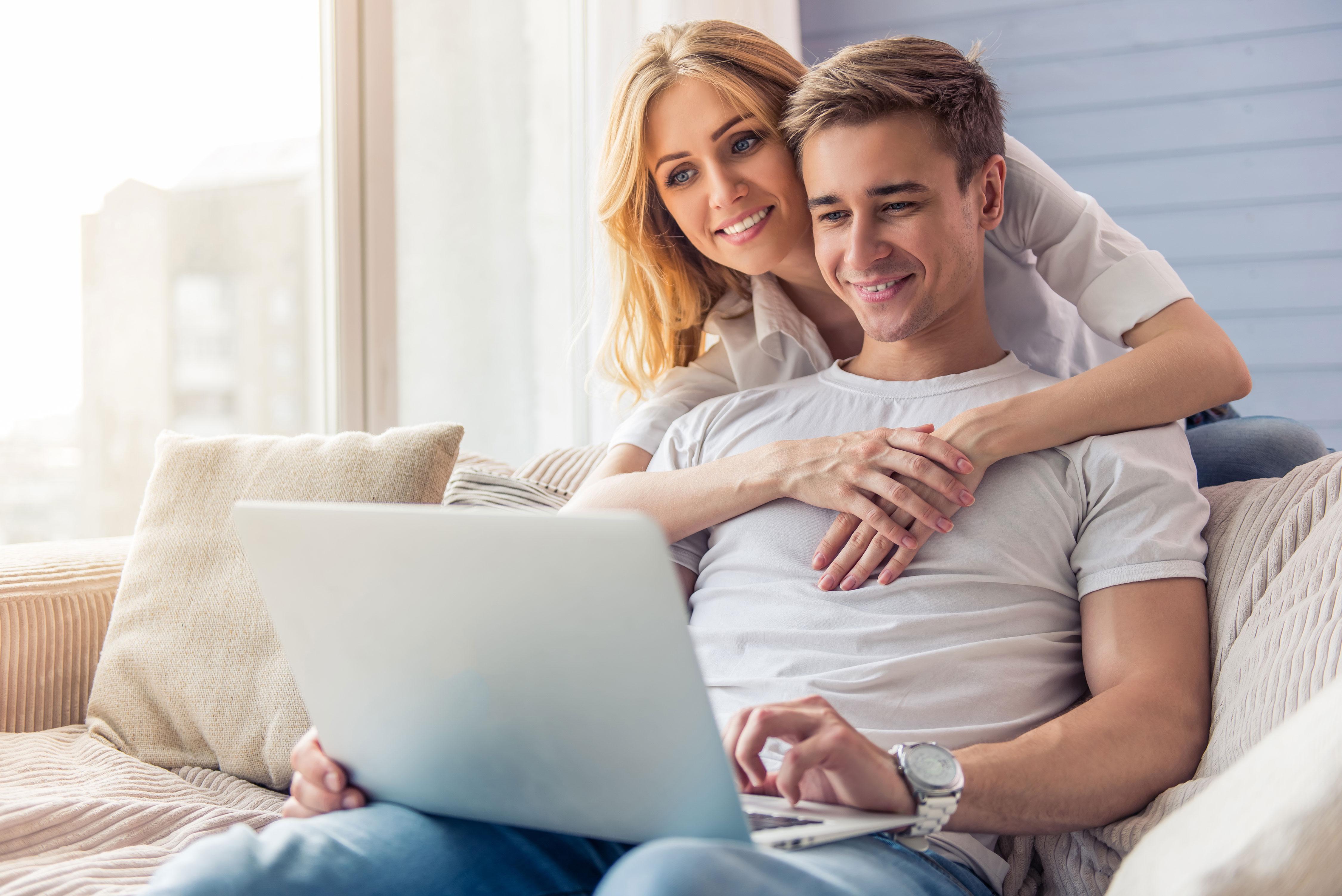 Junges Paar lächelnd auf Sofa mit Laptop