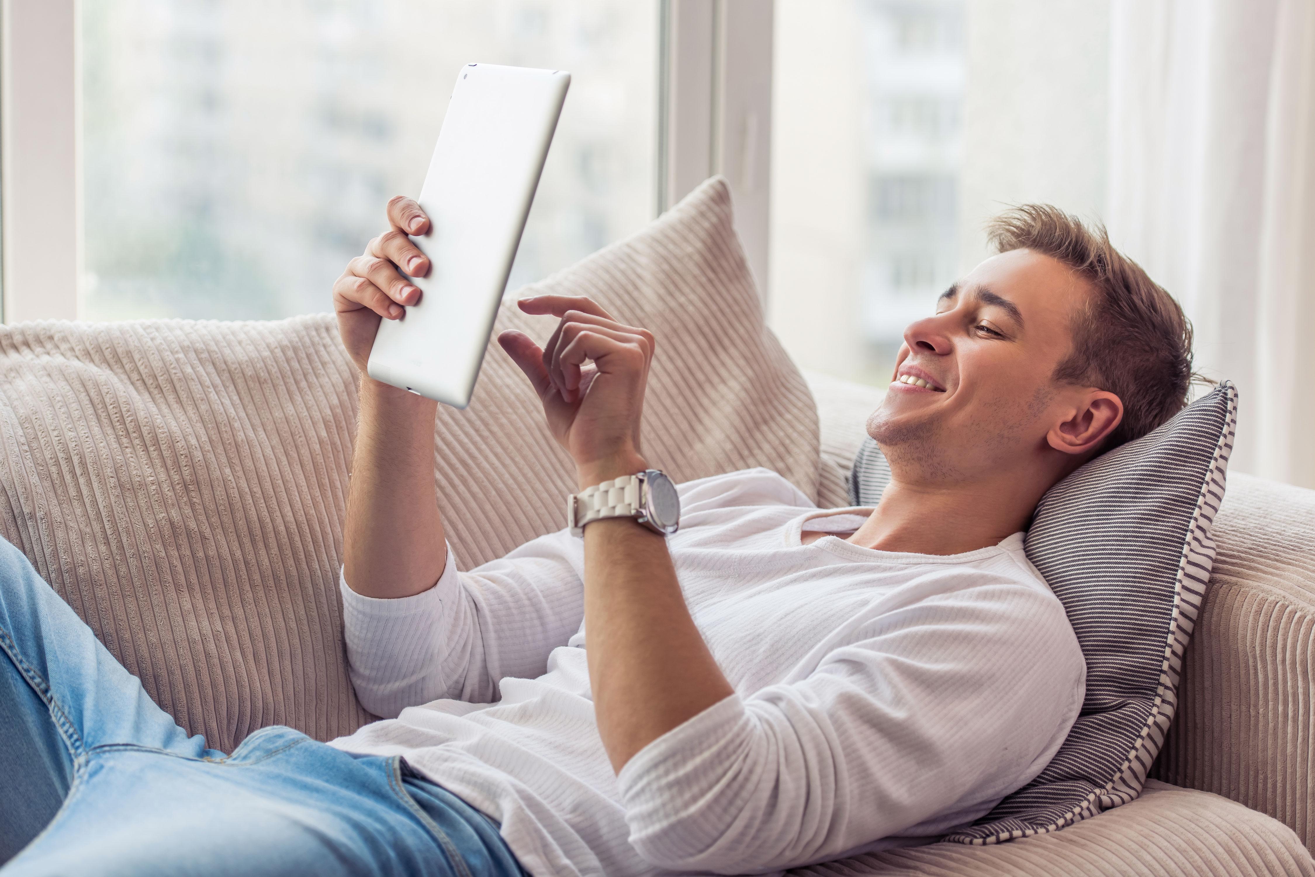 Junger lächelnder Mann auf dem Sofa liegend mit Tablet in der Hand