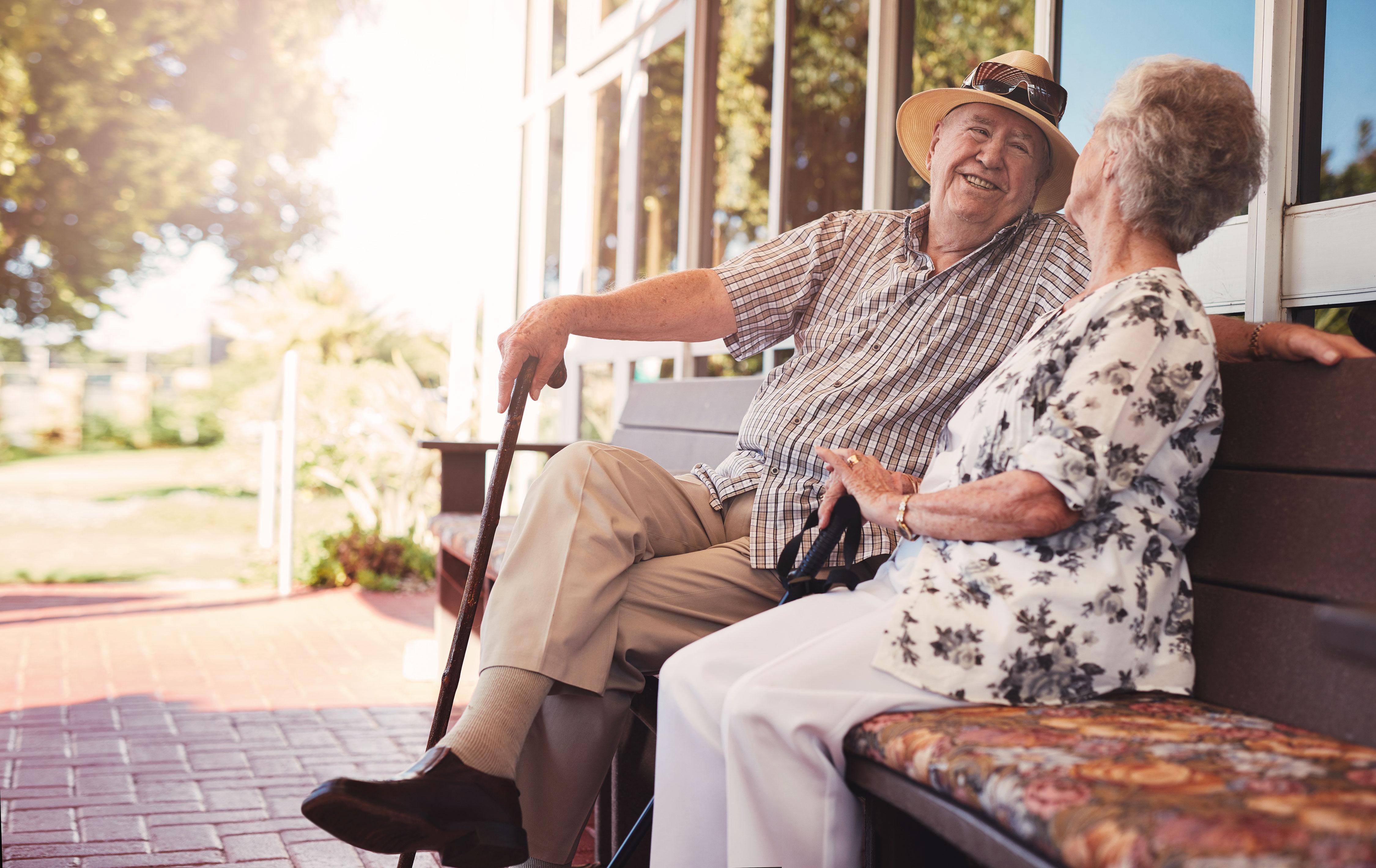 Glückliches älteres Paar sitzt entspannt auf einer Bank vor dem Haus