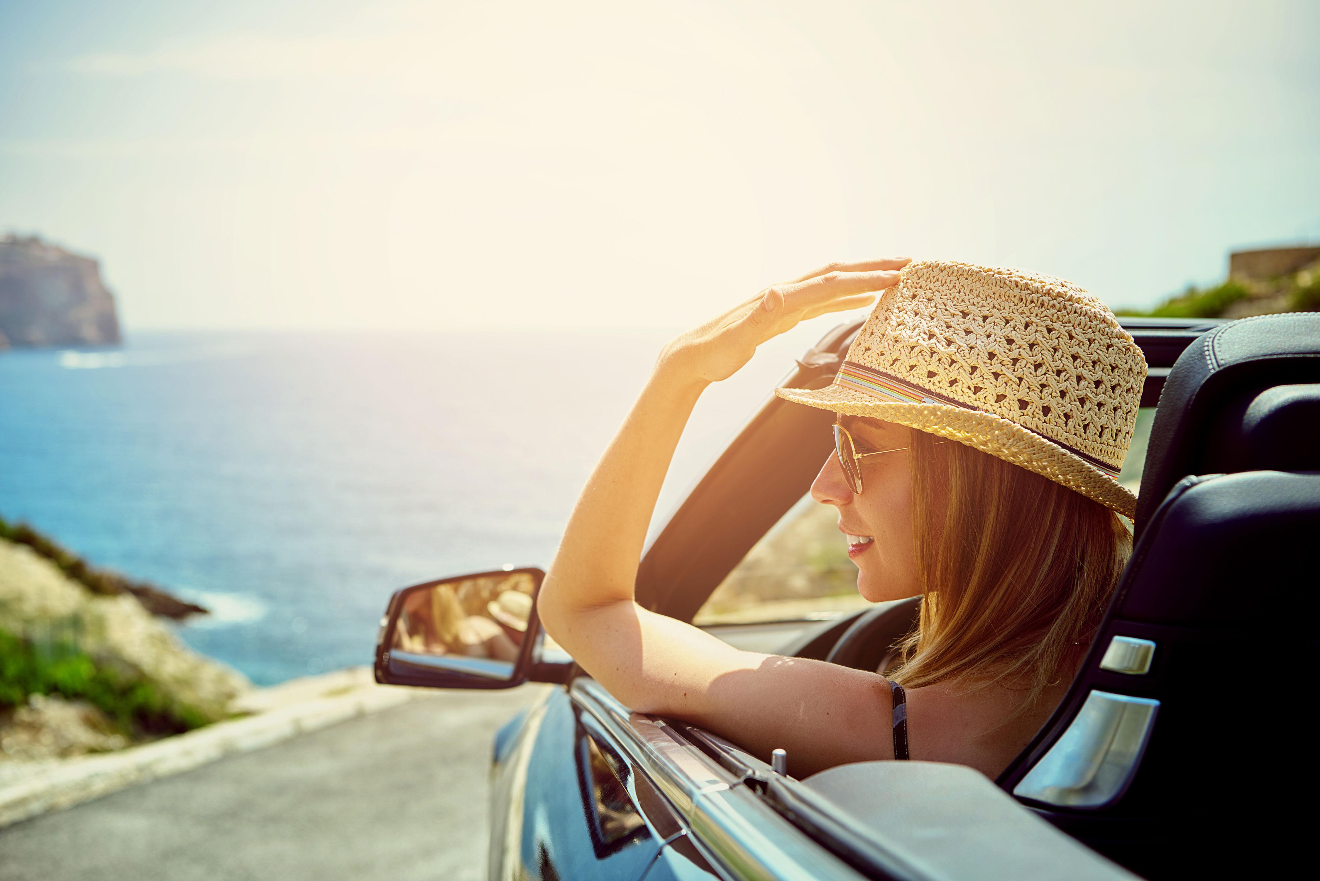 Seitenblick auf lächelnde Frau in Cabrio am Meer im Sonnenschein