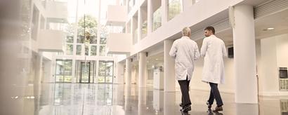 Zwei sich unterhaltende Ärzte von hinten auf dem Weg durch ein modernes Krankenhaus