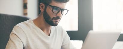Junger Mann mit Brille vor einem Laptop