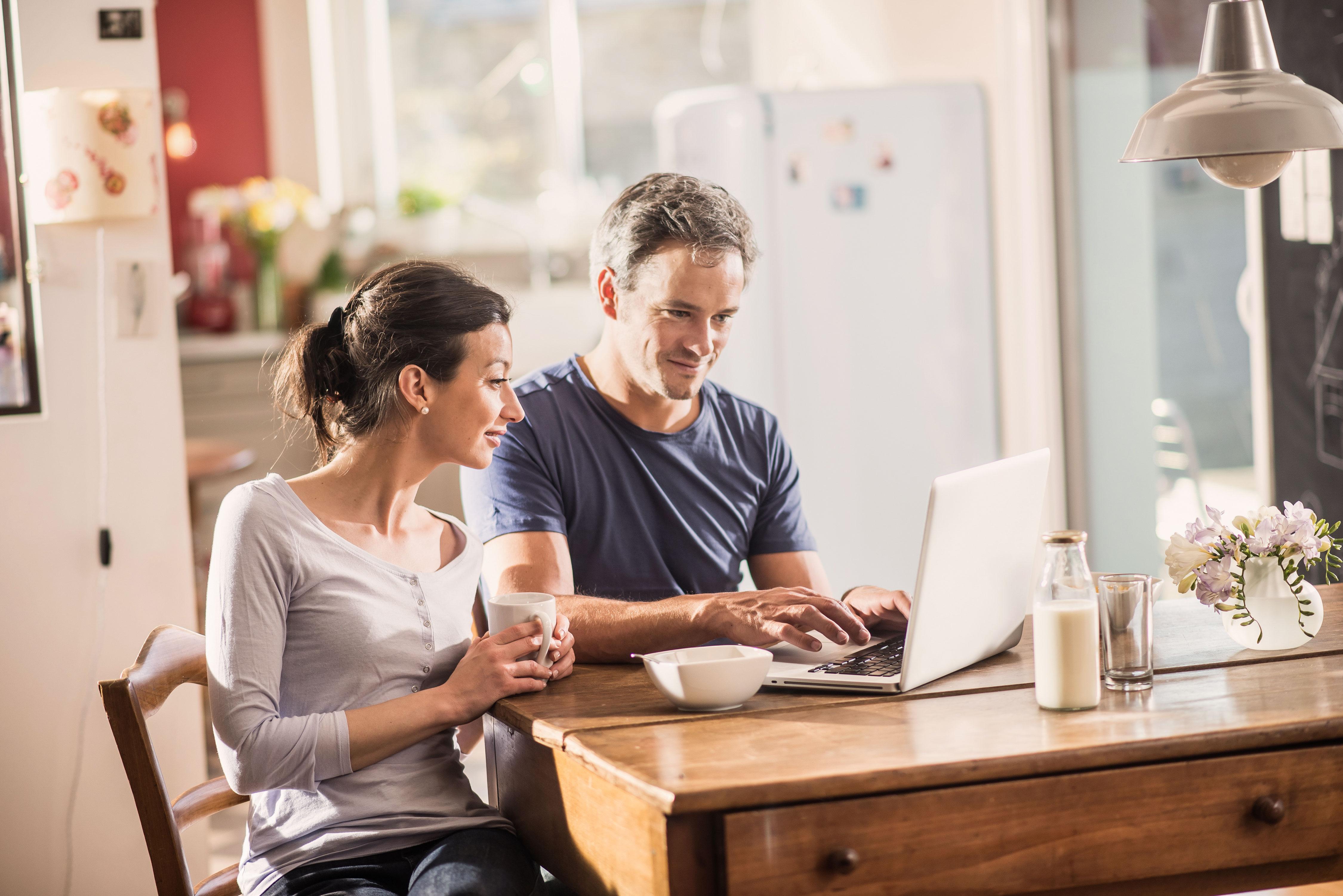 Paar an Küchentisch vor Laptop