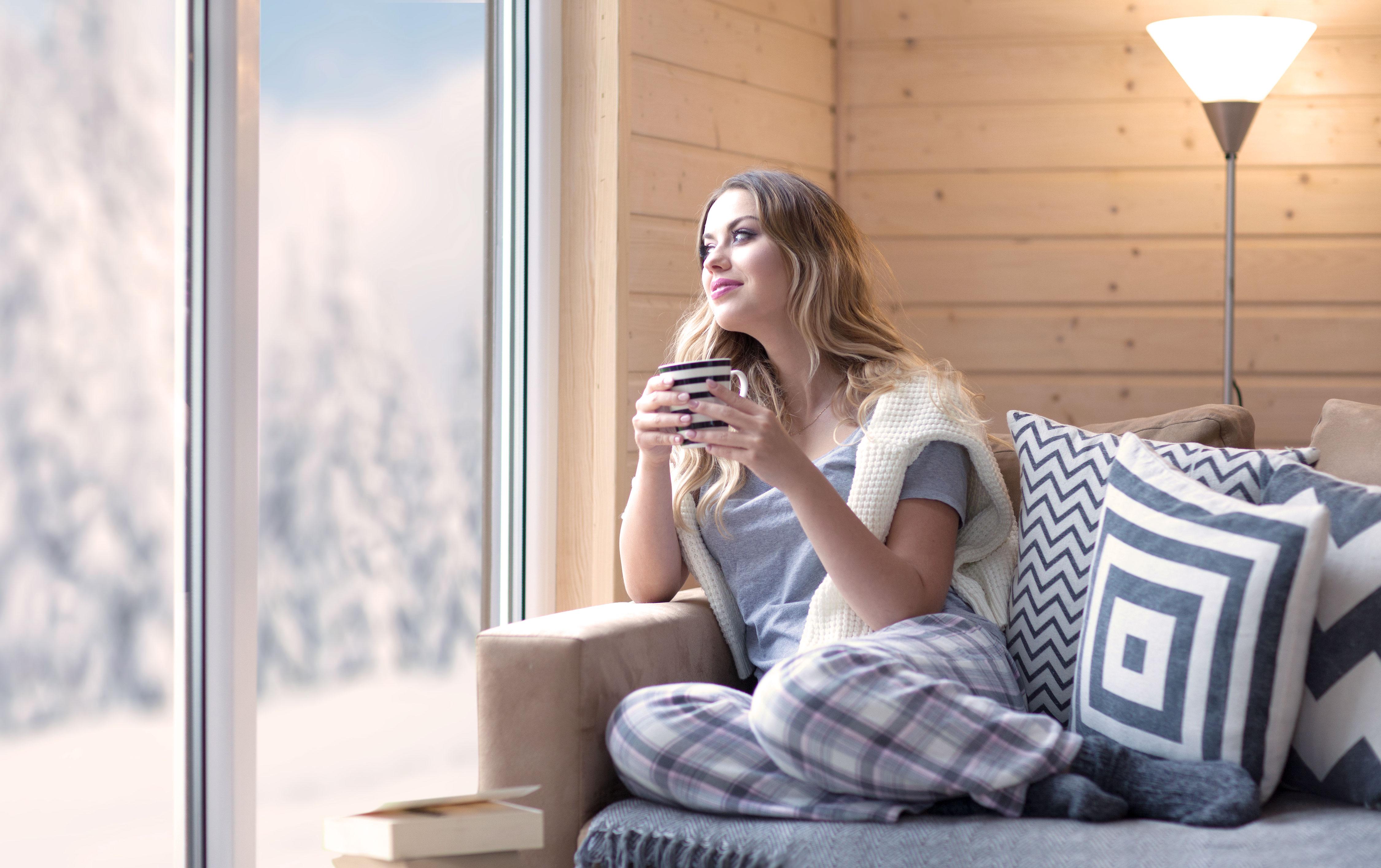 Junge blonde Frau sitzt mit Kaffeetasse auf dem Sofa und schaut aus dem Fenster in die Schneelandschaft