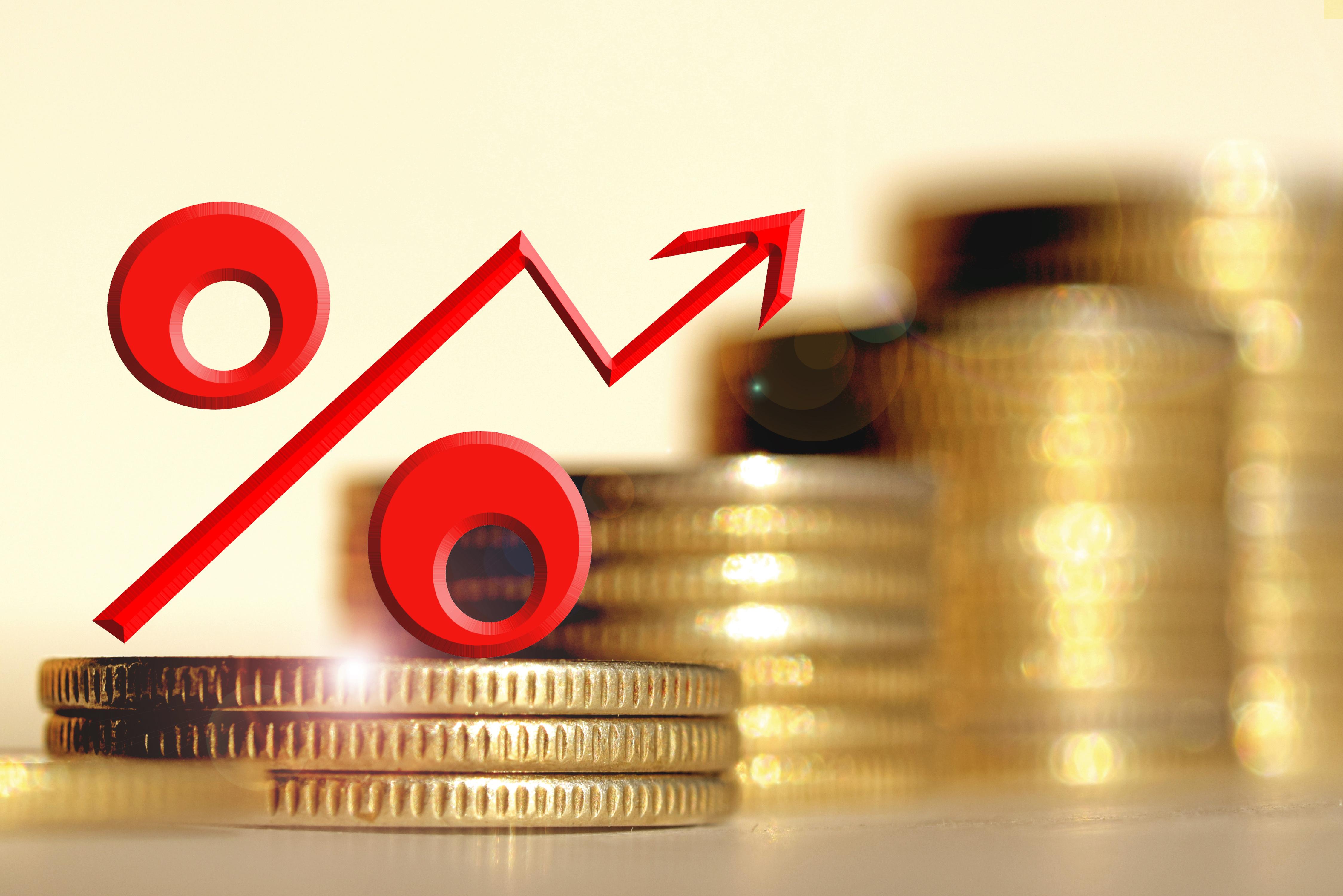 Rotes Prozentzeichen auf gestapelten Münzen
