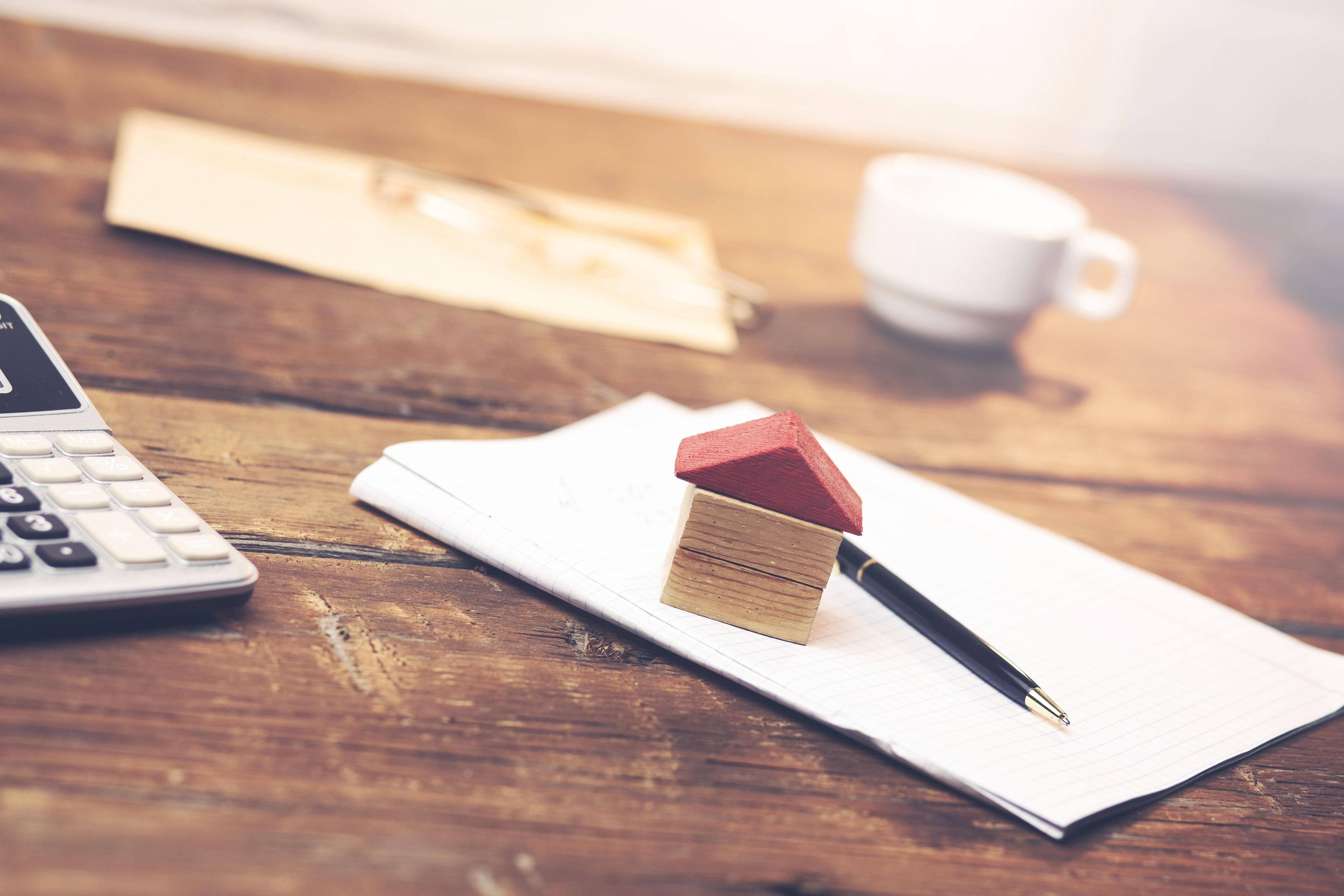 Haus aus Holzblöcken auf Notizblock auf Holztisch
