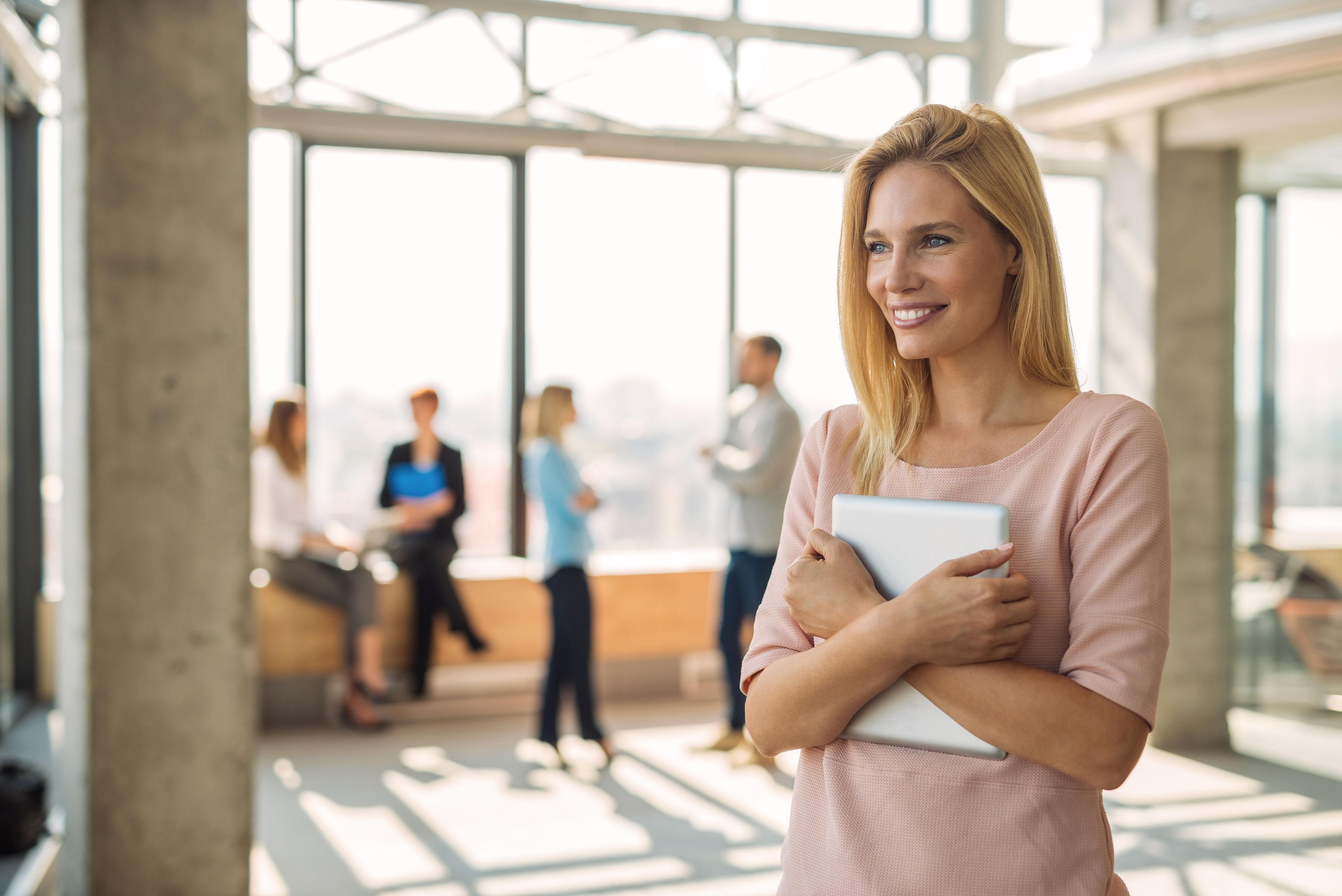 Lächelnde Frau mit Tablet im Arm in lichtdurchflutetem Büro