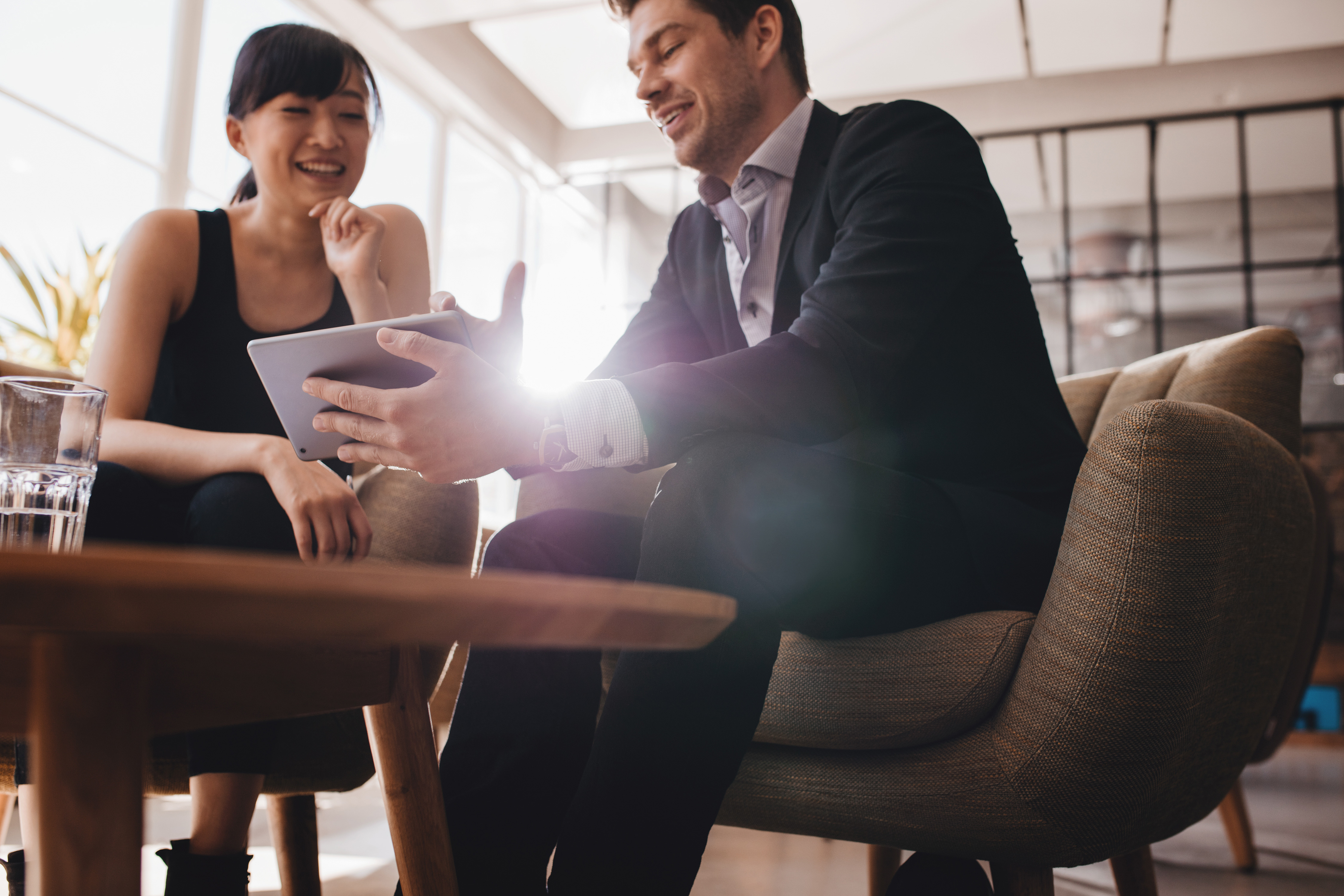 Geschäftpartner besprechen ein Projekt am Tablet.