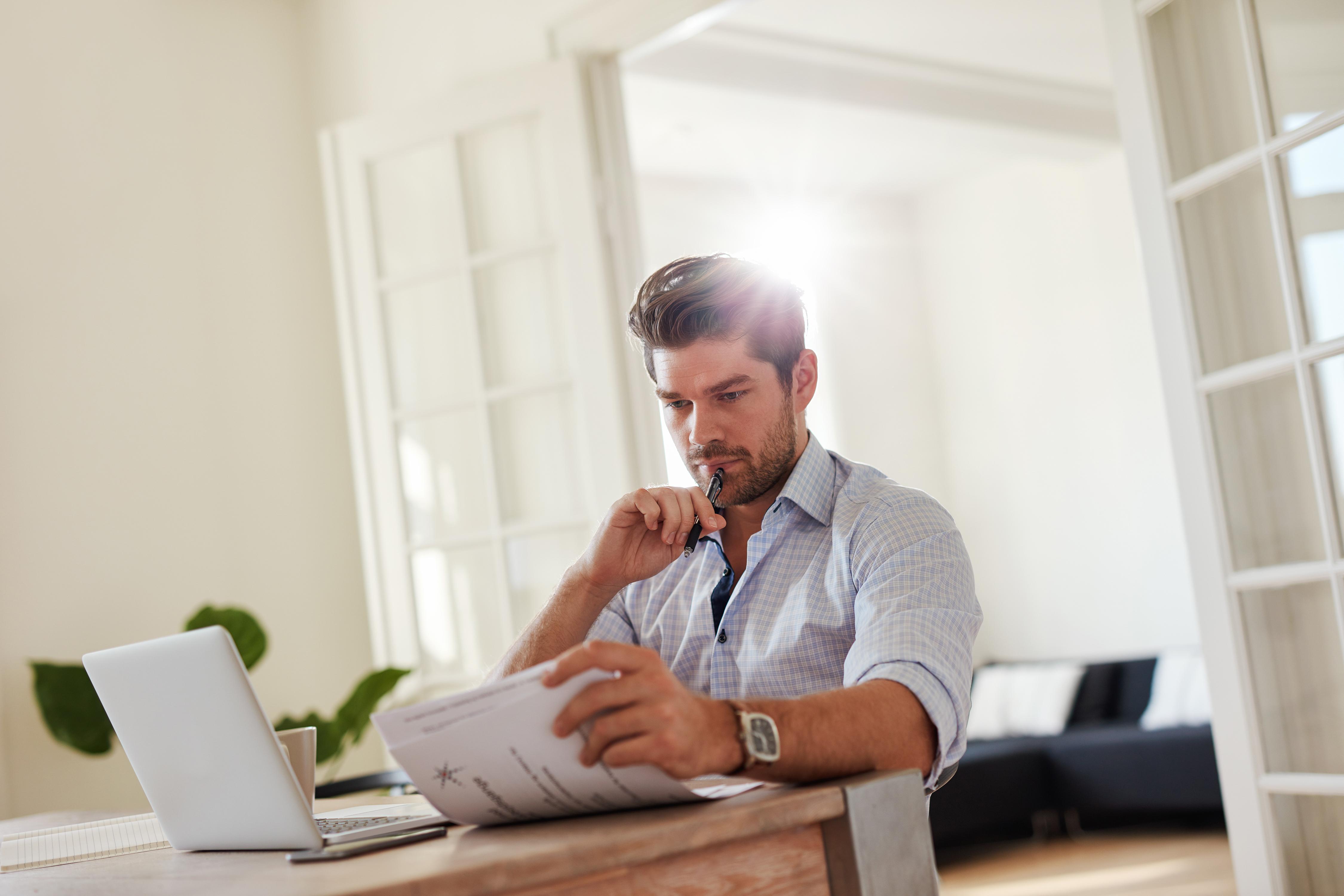 Junger Mann liest Dokumente zu Hause vor seinem Laptop